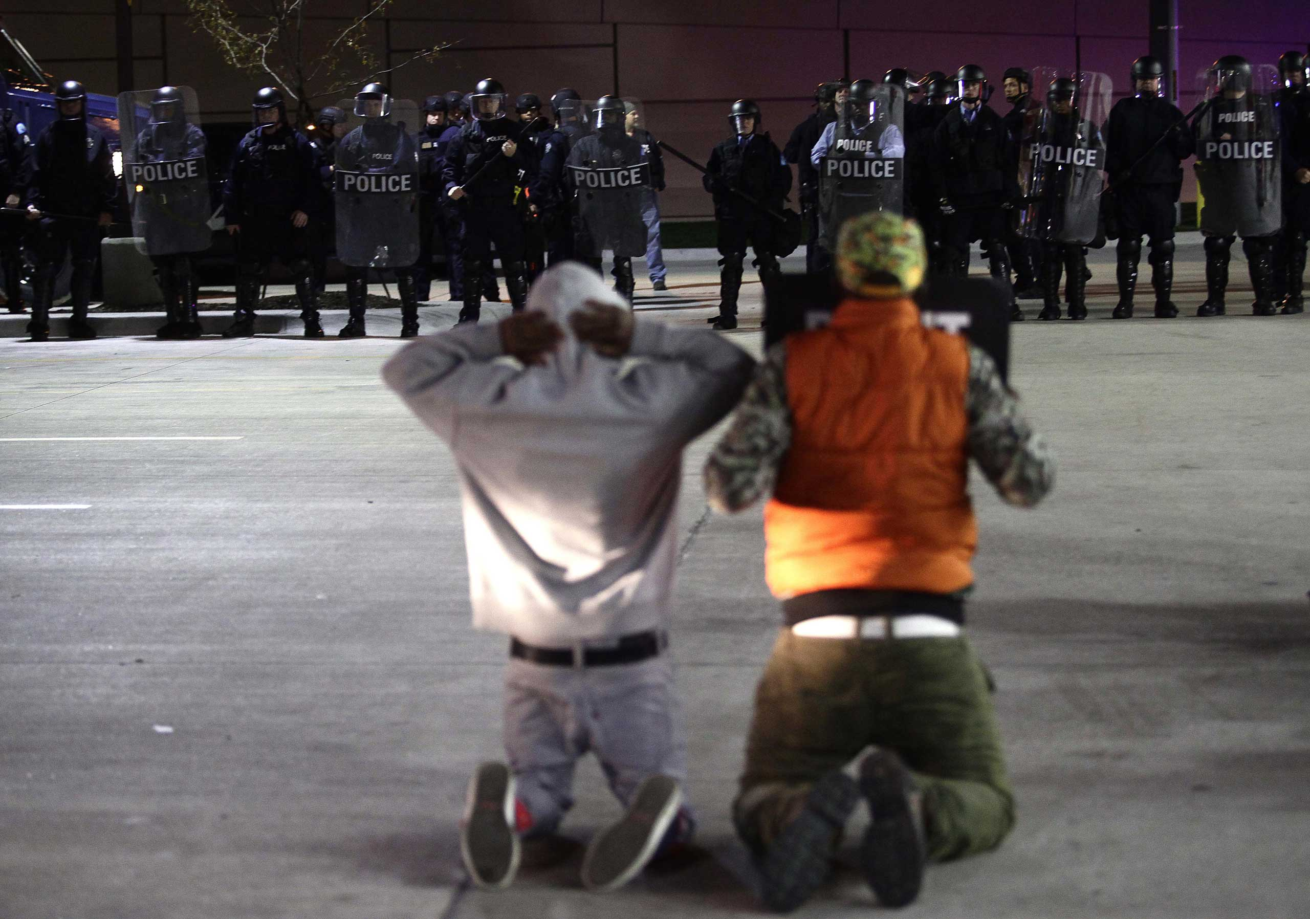 Demonstrator protesting the shooting death of Michael Brown and Vonderrit Myers Jr. kneel as they face police officers in riot gear in St. Louis on Oct. 12, 2014.