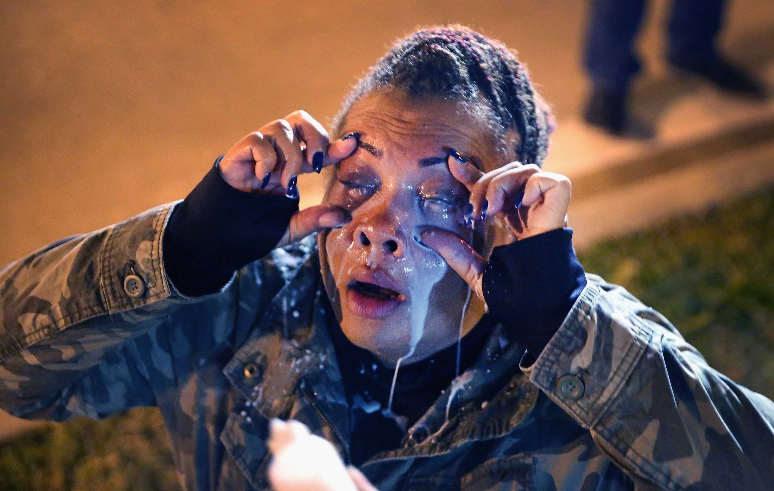 A demonstrator gets help after being maced by police in St. Louis on Oct. 12, 2014.