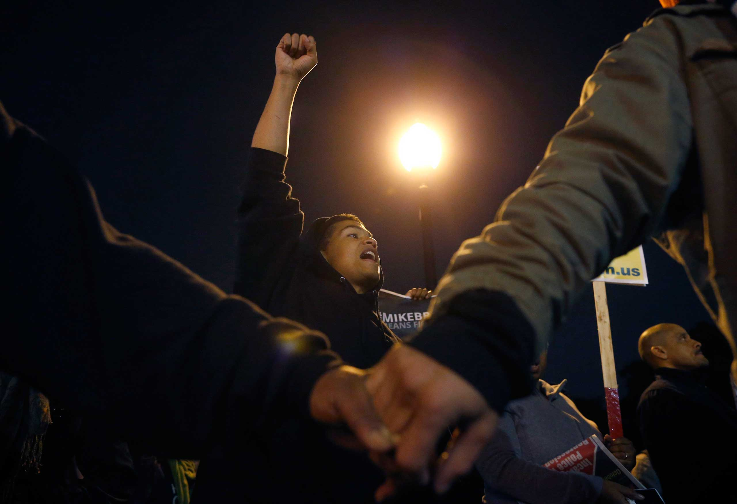 Protesters hold hands and demonstrate across the street from the Ferguson Police Department in Ferguson, Mo. on Oct. 10, 2014.