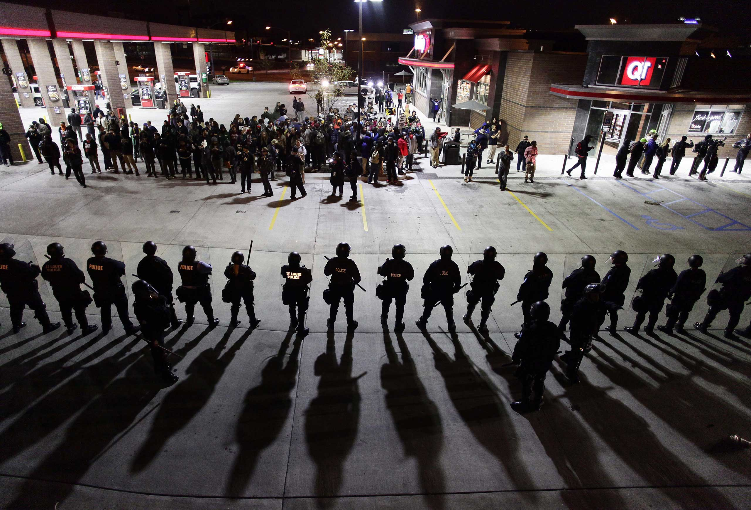 Police officers in riot gear hold a line as they watch demonstrators protest in St. Louis on Oct. 12, 2014.