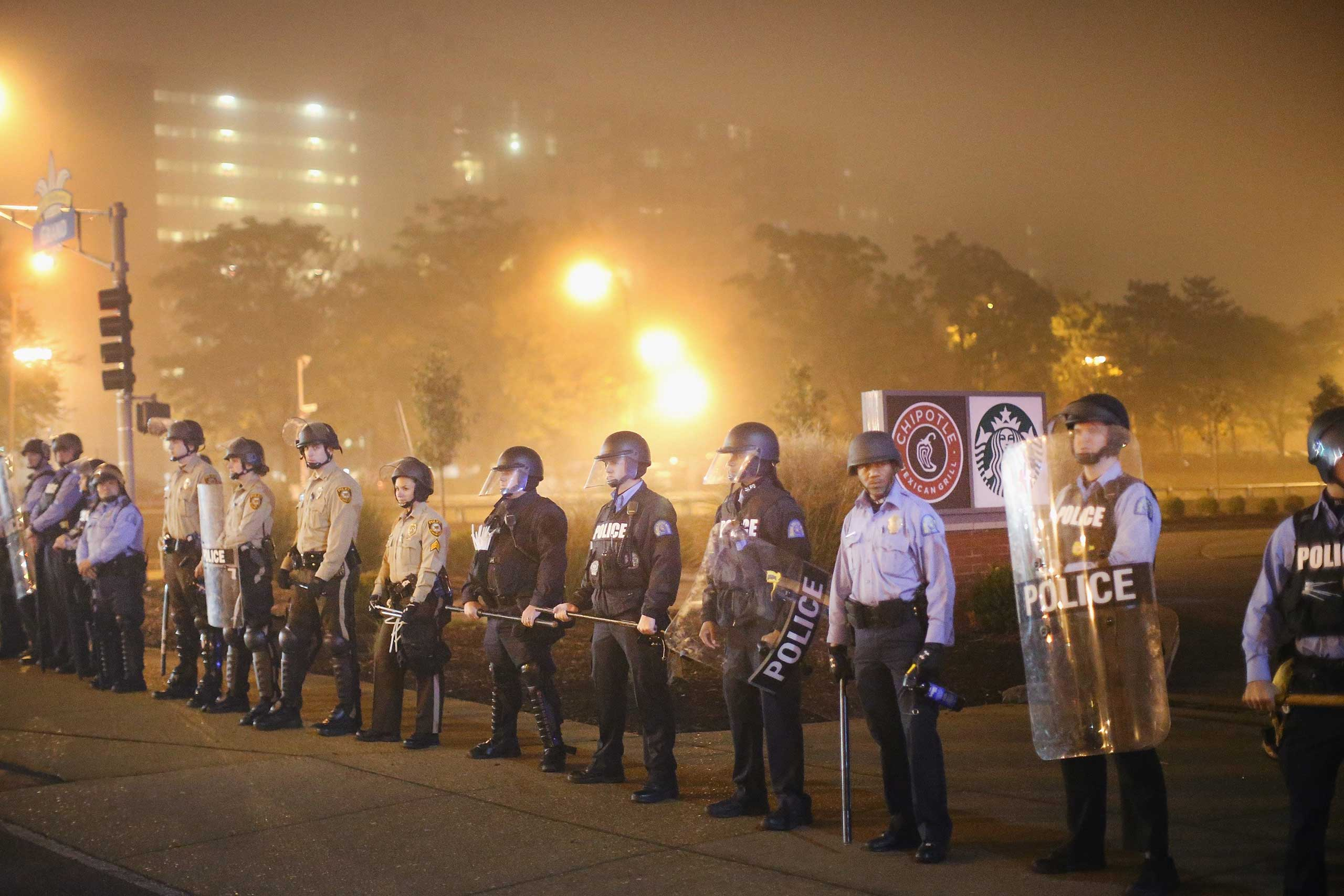 Police stand guard as demonstrators march through the streets of St. Louis on Oct. 13, 2014.