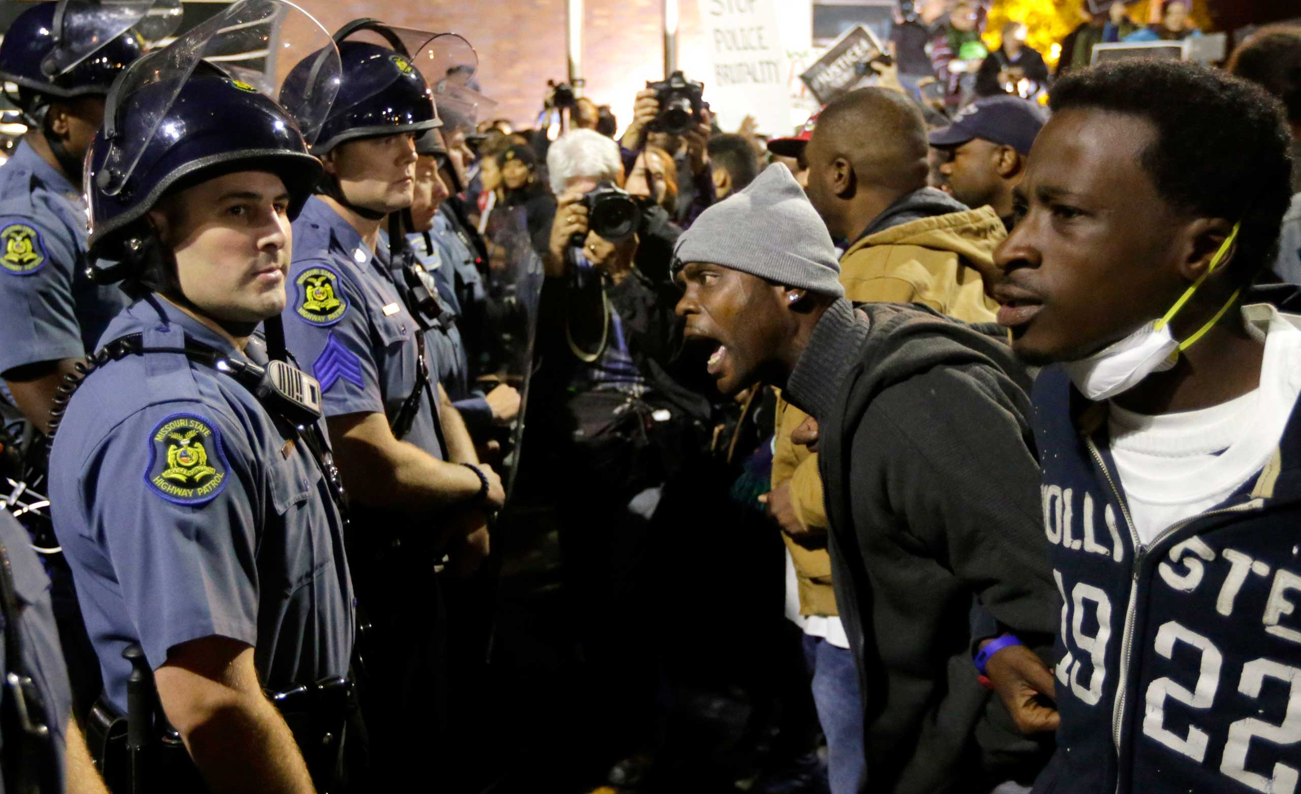 A protester yells at a Missouri State Police officer during a protest at the Ferguson Police Department in Ferguson, Mo. on Oct. 10, 2014.