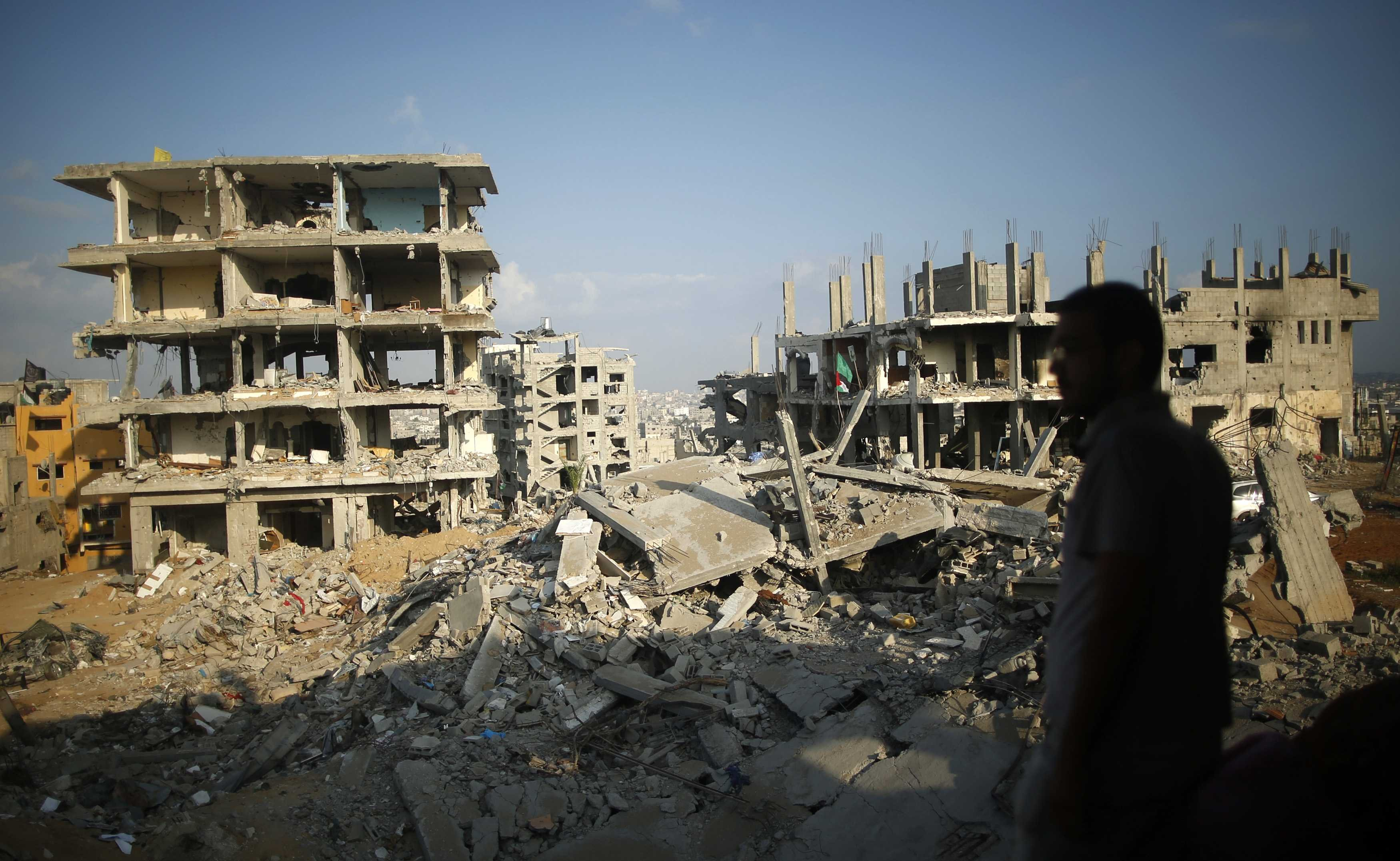 A Palestinian man stands atop the rubble of his house as he looks at the ruins of his neighborhood that was badly damaged during the 50-day war between the Hamas militant movement and Israel, in the east of Gaza City on Oct. 12, 2014.