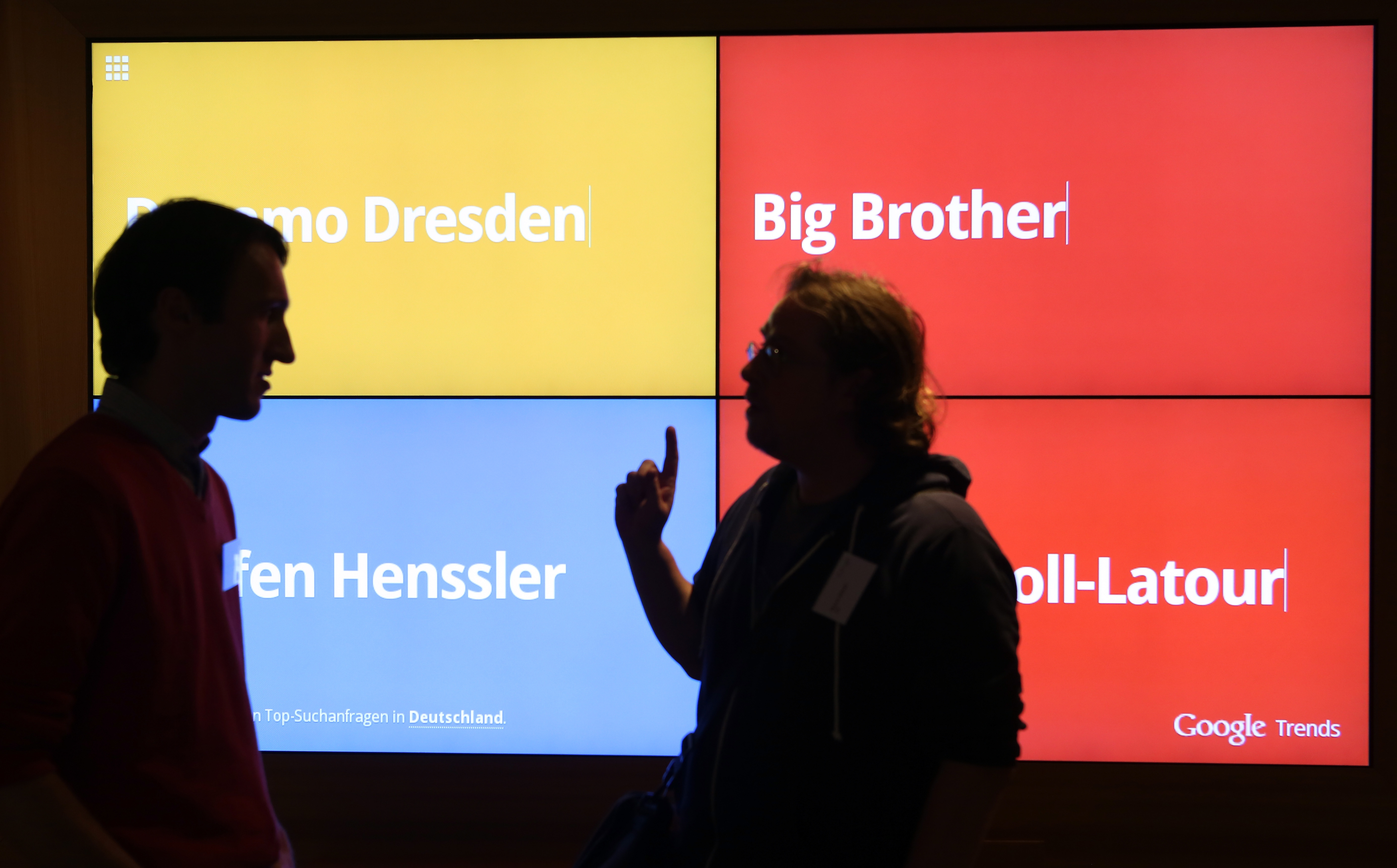 Visitors stand in front of a screen showing the most popular Google searches in Germany at that moment in the company's offices on Aug. 21, 2014 in Berlin.