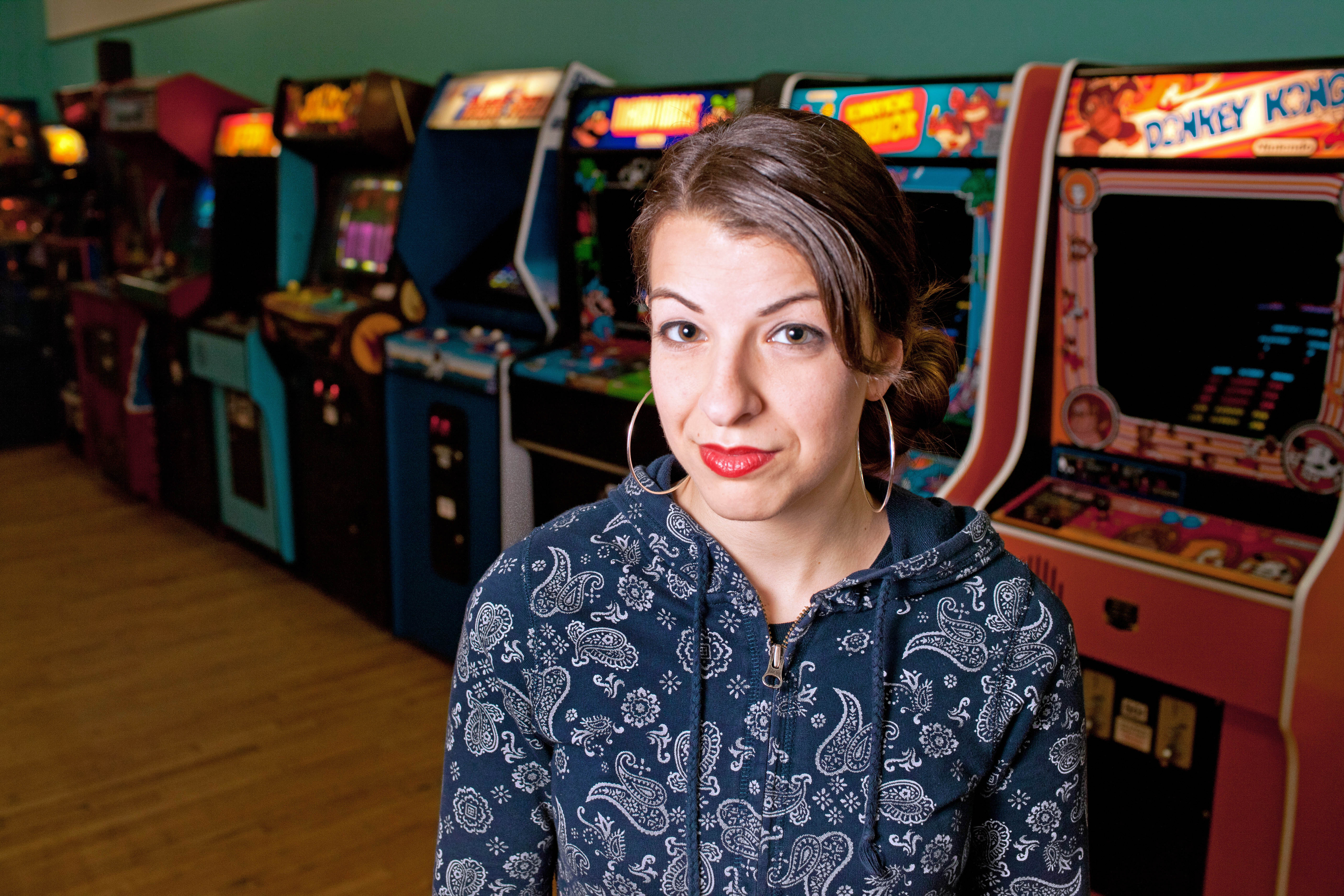 This Jan. 17, 2013, photo provided by Anita Sarkeesian shows her with vintage video game machines in MInneapolis.