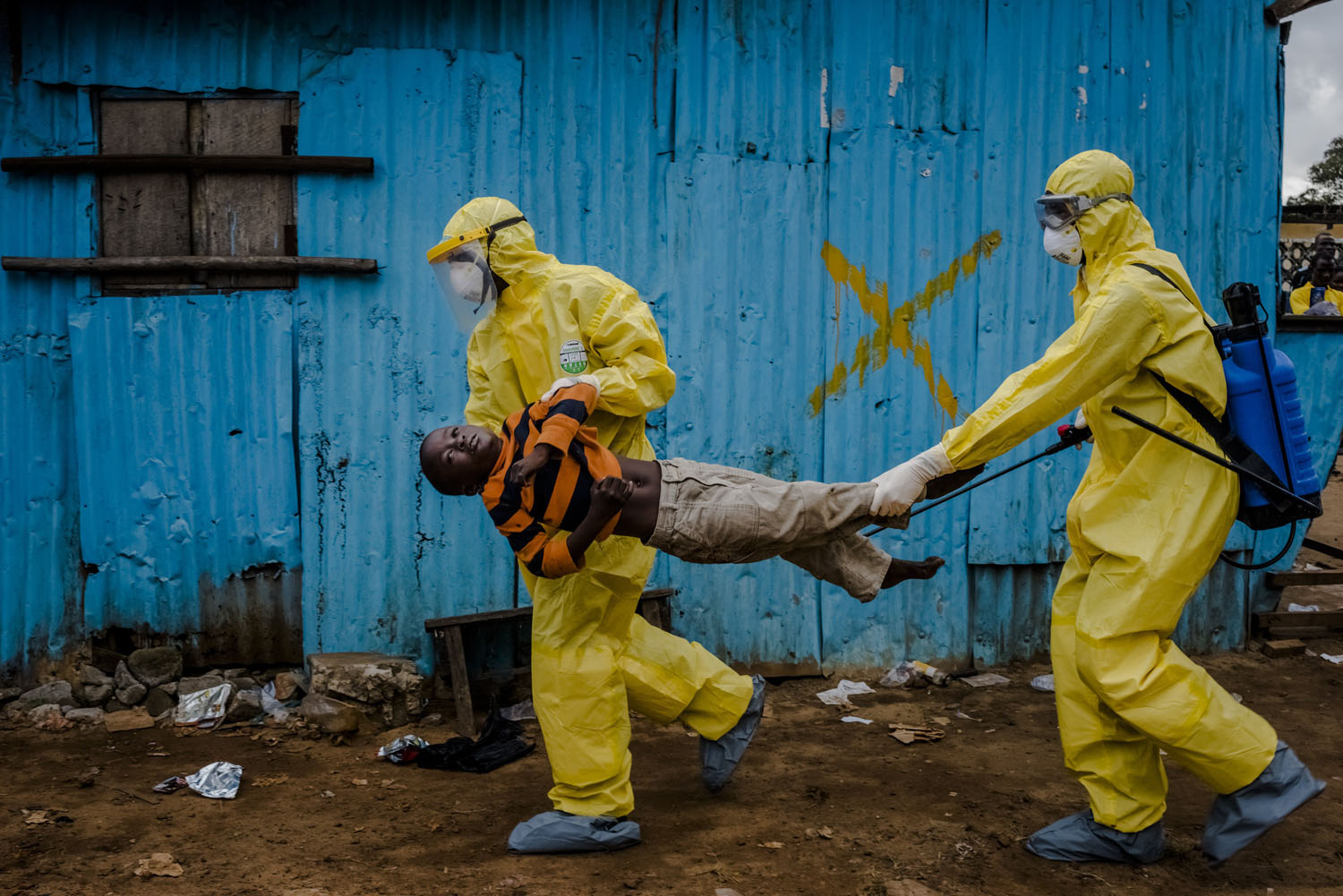 Medical staff rush into the treatment facility, carrying James Dorbor, 8, suspected of having Ebola. Since the health workers weren't wearing the appropriate protection against Ebola, they positioned James' body in a way to limit exposure to the deadly virus. Monrovia, Liberia, Sept. 5, 2014.