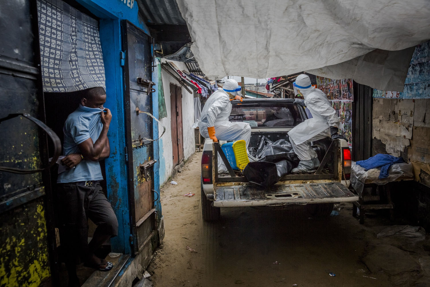 A resident of the West Point neighborhood covers his nose as a burial team leaves with a body in Monrovia, Liberia, Sept. 17, 2014.