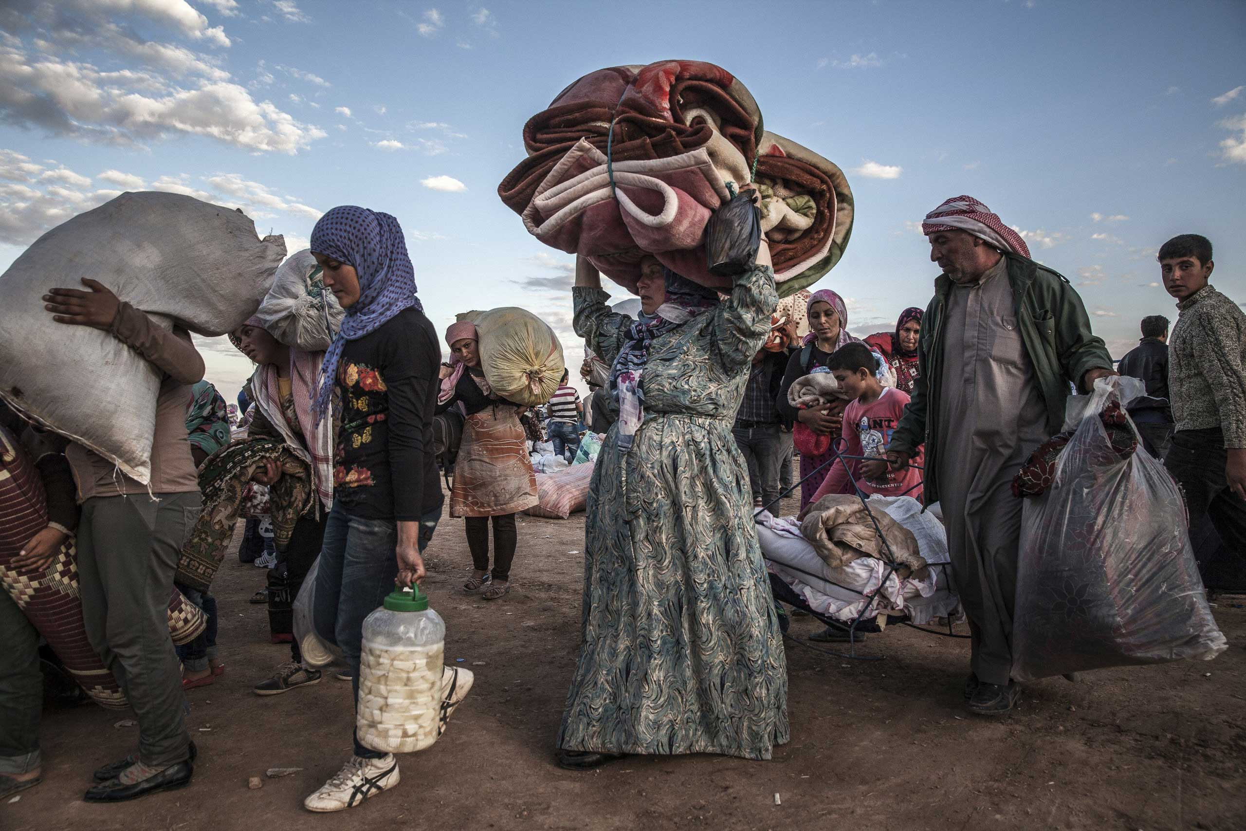 Sept. 29, 2014. Syrian Kurdish refugees at the Yumurtalik border crossing wait to be taken to shelters elsewhere in Turkey. Islamic State militants have been carrying out a weeklong assault on the Kurdish area across the border, where residents have pleaded for military aid.