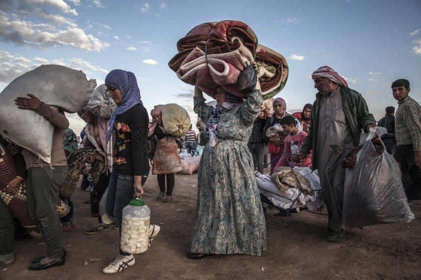 Syrian Kurdish refugees at the Yumurtalik border crossing wait to be taken to shelters elsewhere in Turkey.