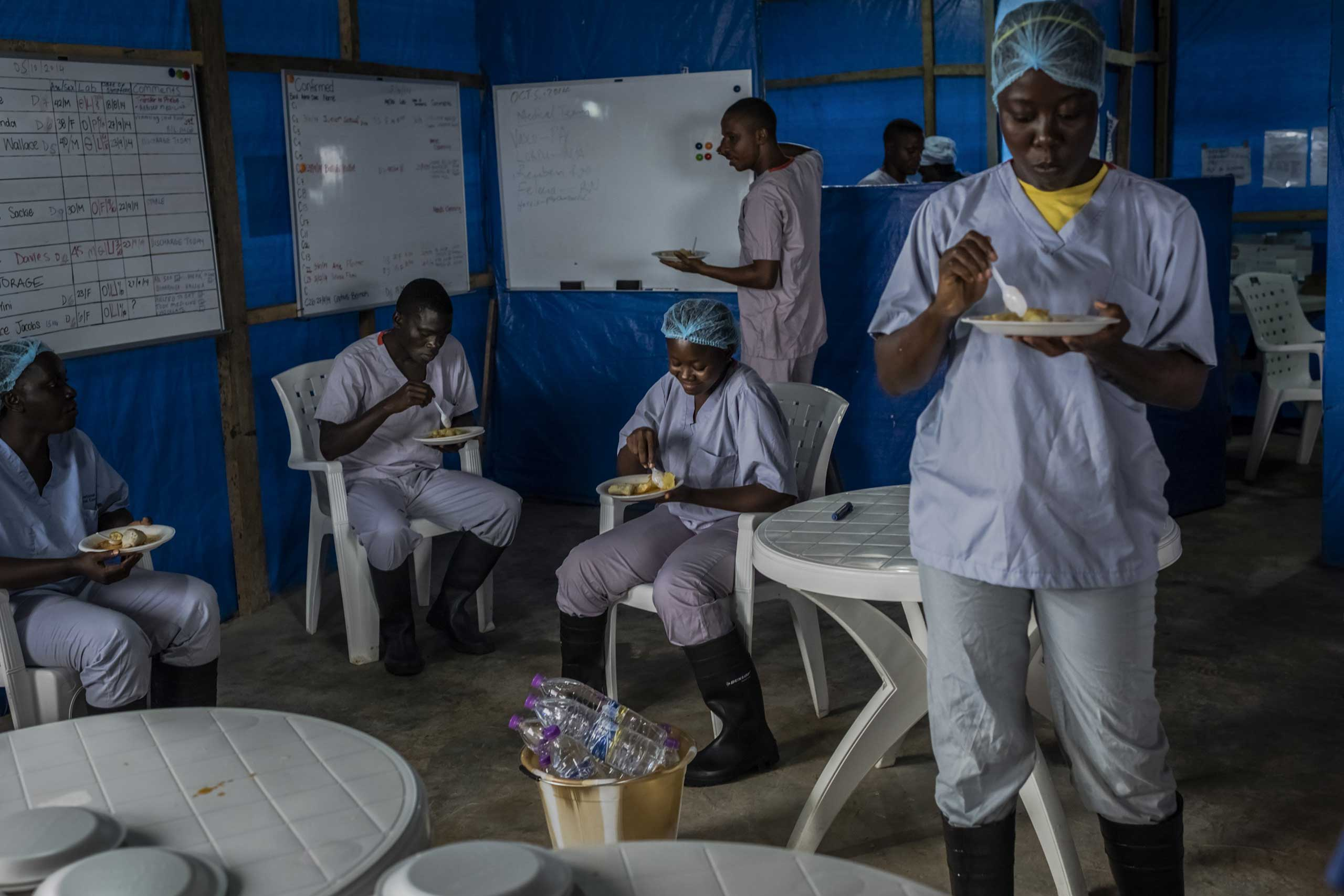 Oct. 5, 2014. Health workers eat breakfast at the Bong County Ebola Treatment Unit near Gbarnga in rural Bong County, Liberia. The food is prepared off site, at a university that is closed because of the Ebola outbreak and houses many of the staff members.