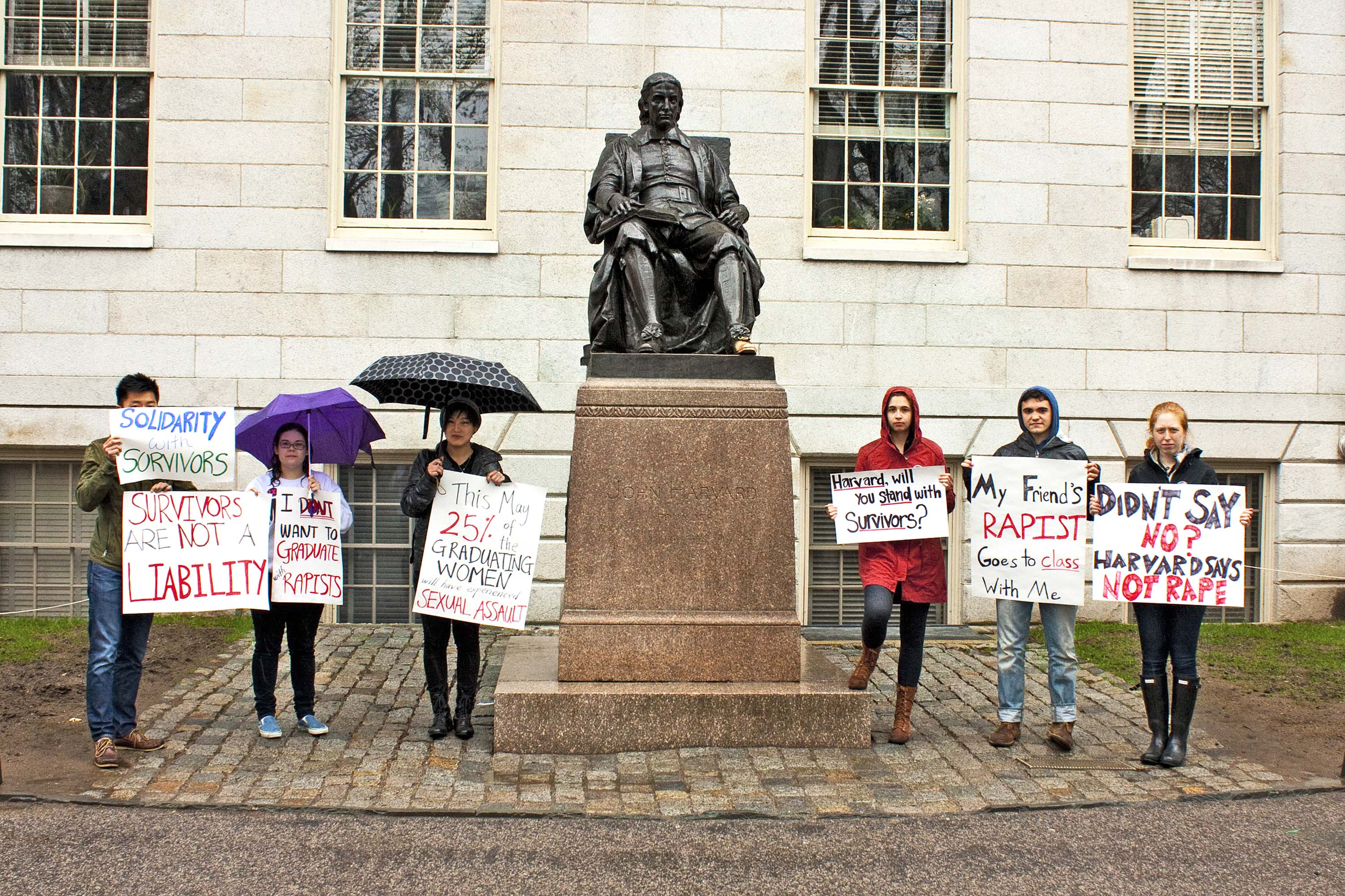 Students protest Harvard's handling of sexual-assault allegations in front of a statue of John Harvard in April.