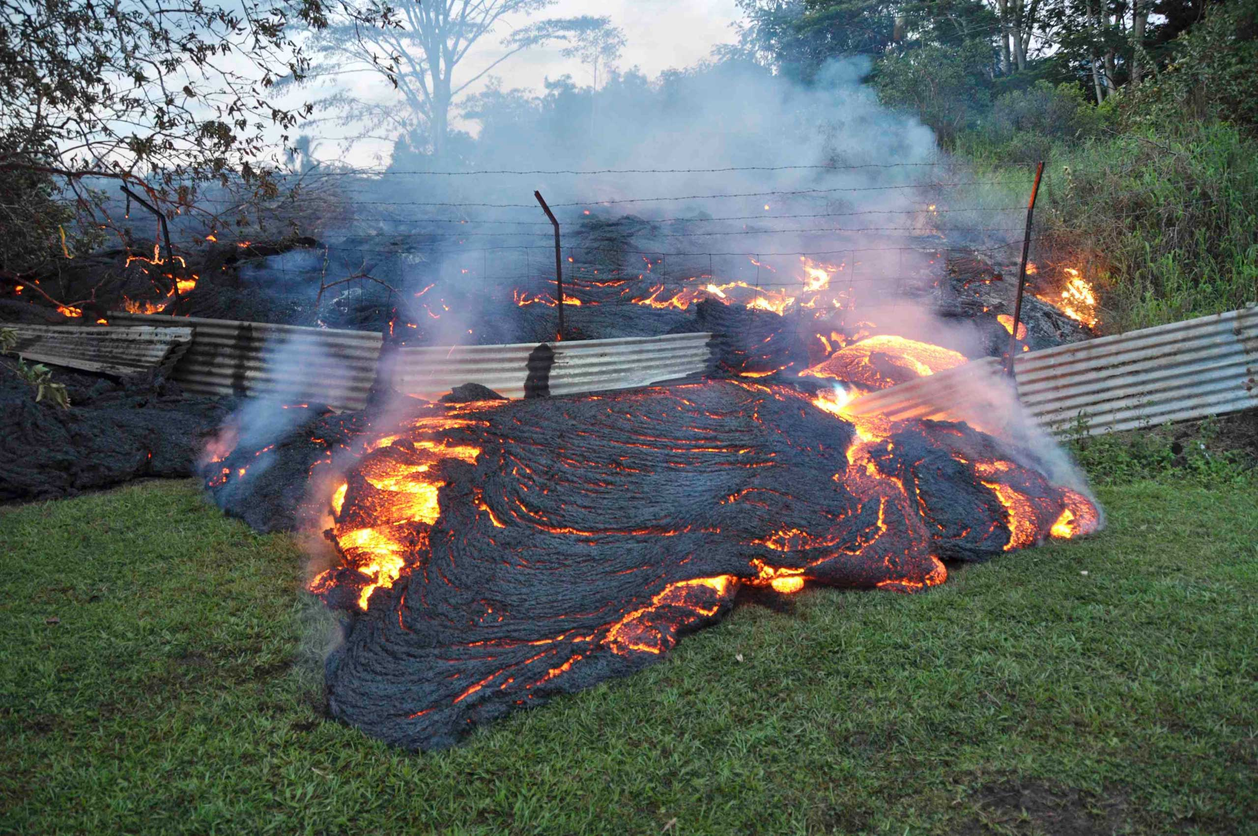 The lava flow from the Kilauea Volcano burns vegetation as it approaches a property boundary near the village of Pahoa, Hawaii, on Oct. 28, 2014.