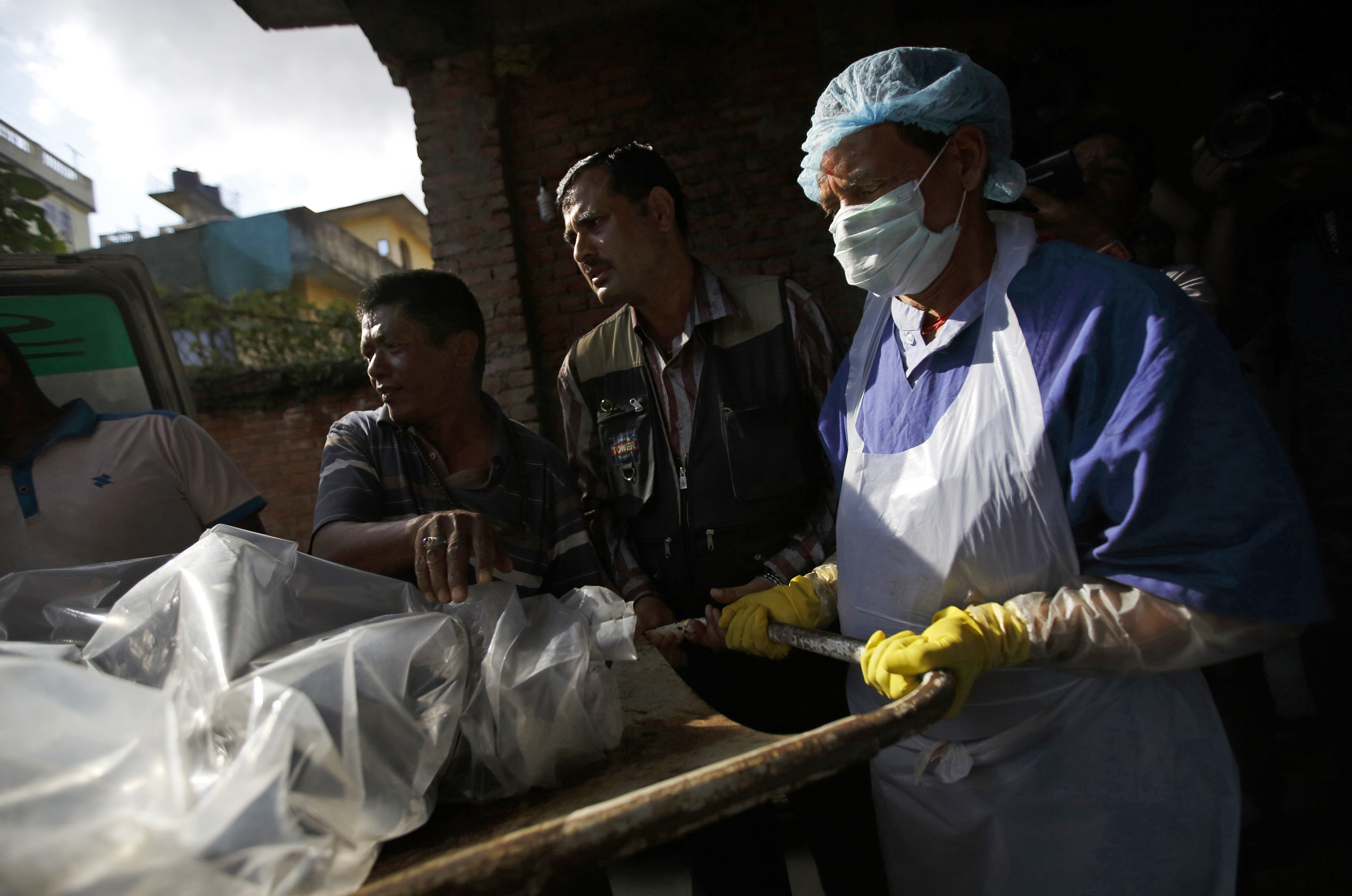 The body of a victim is moved from an ambulance to the morgue after it was brought back from Annapurna Region in Kathmandu October 17, 2014.