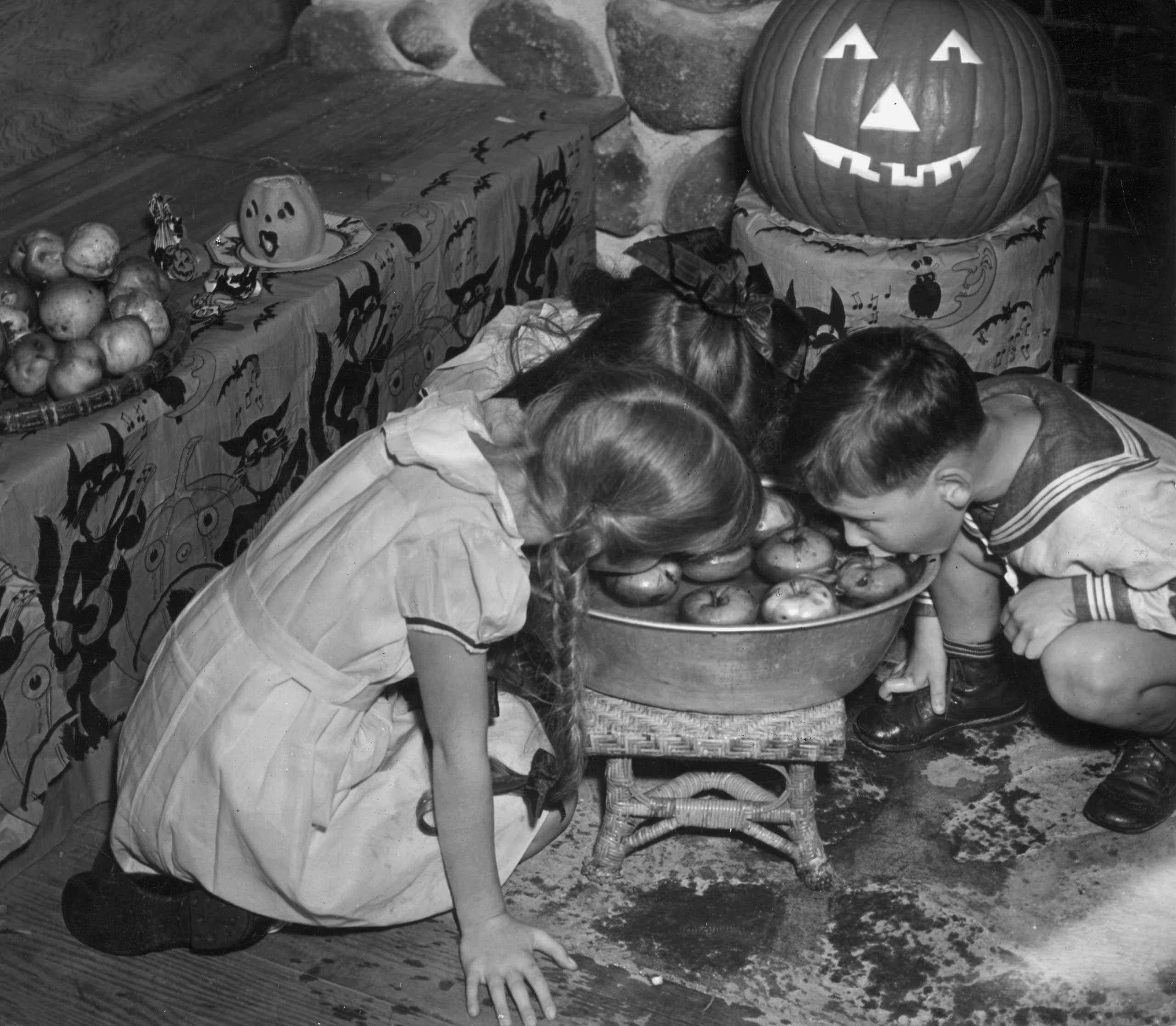 A young boy and girl crouch and bob for apples on Halloween circa 1935.