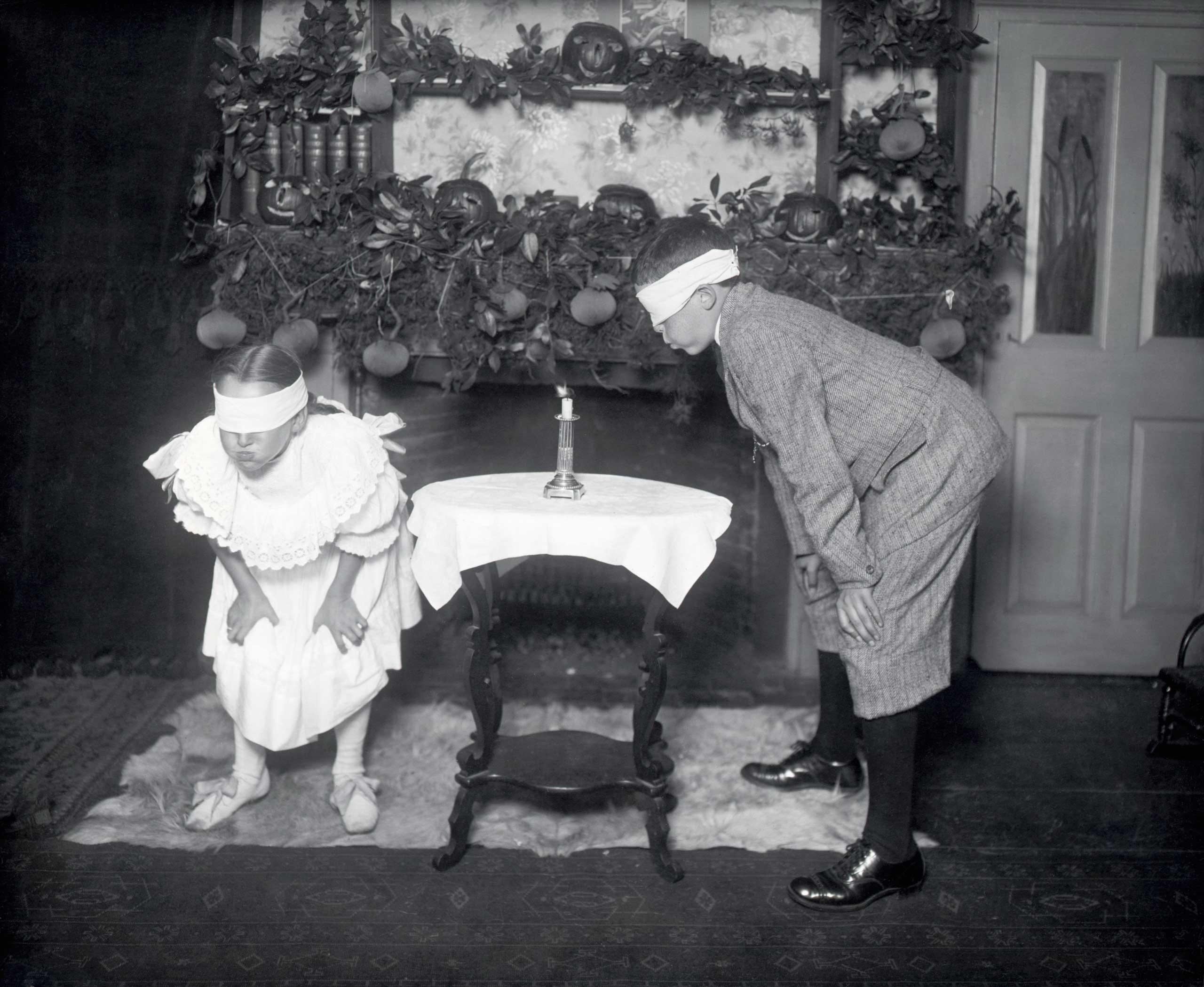 Blindfolded children search for a candle to try to blow it out in an old Halloween tradition circa 1900s.