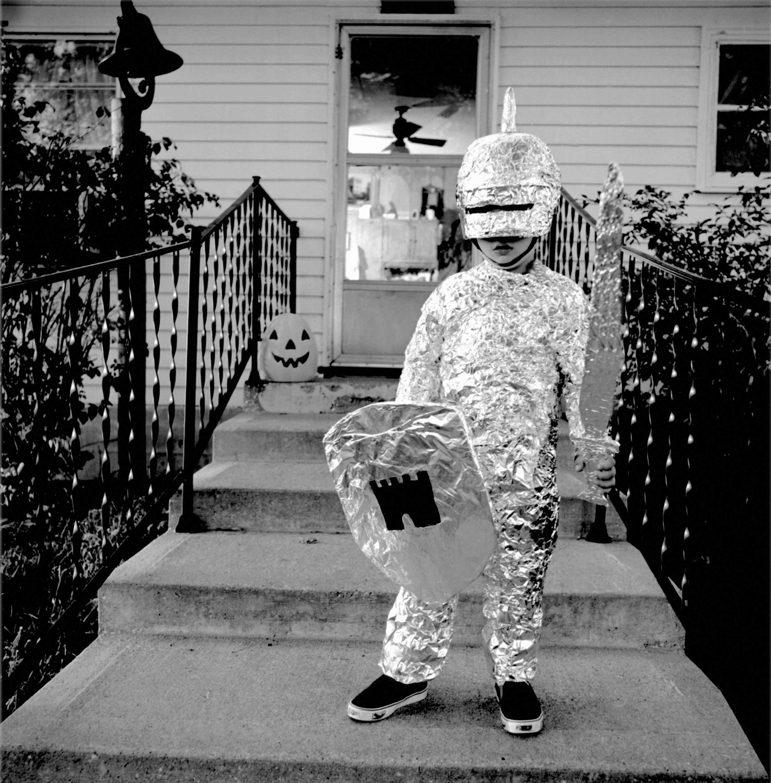 A boy wears a knight costume.