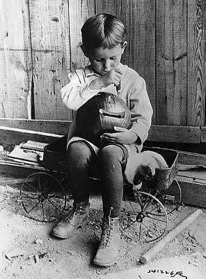A boy carves his pumpkin for Halloween circa 1900s.