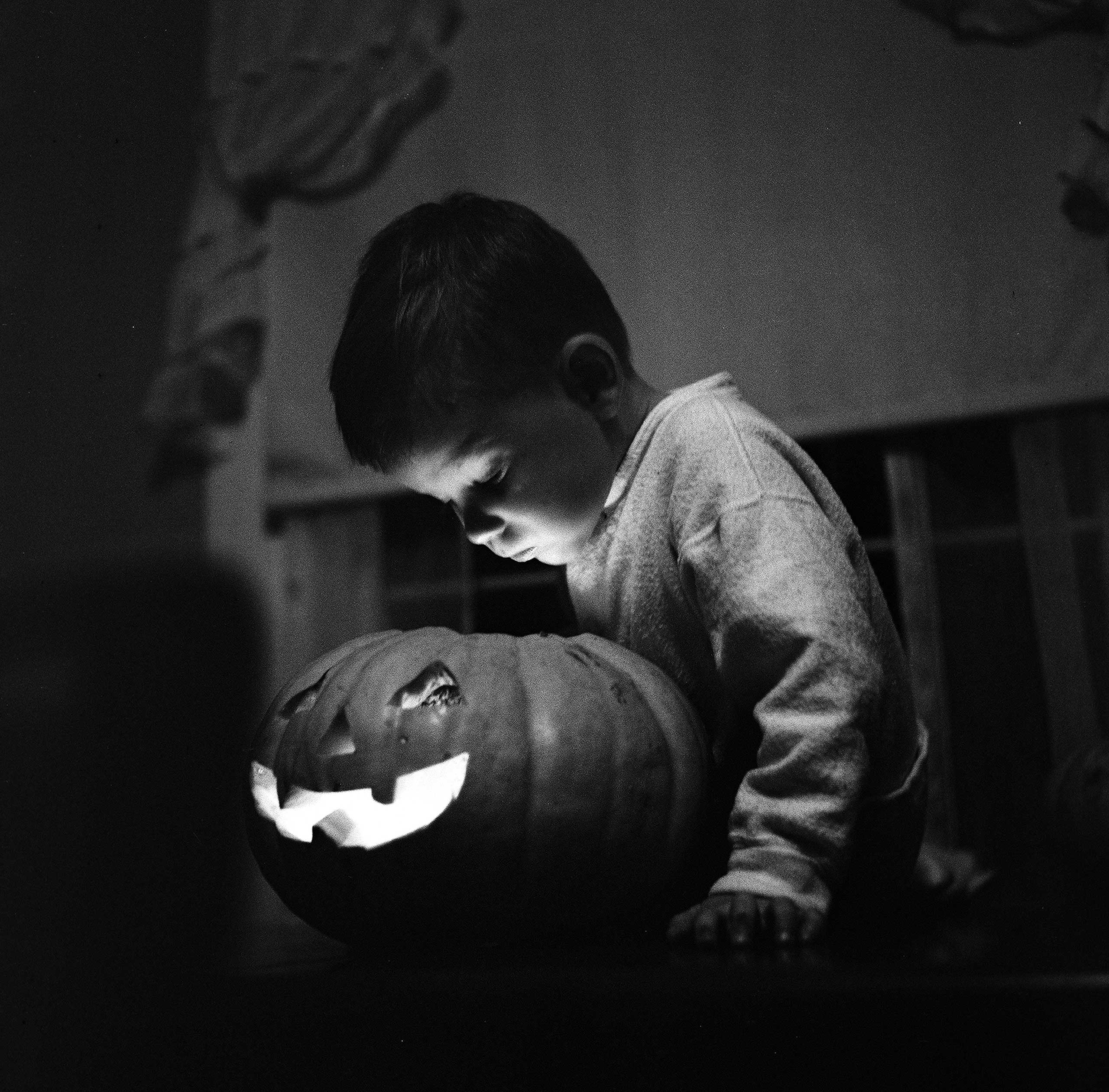 A young boy looks at a lit jack-o-lantern that he helped carve for Halloween, New York, 1949.