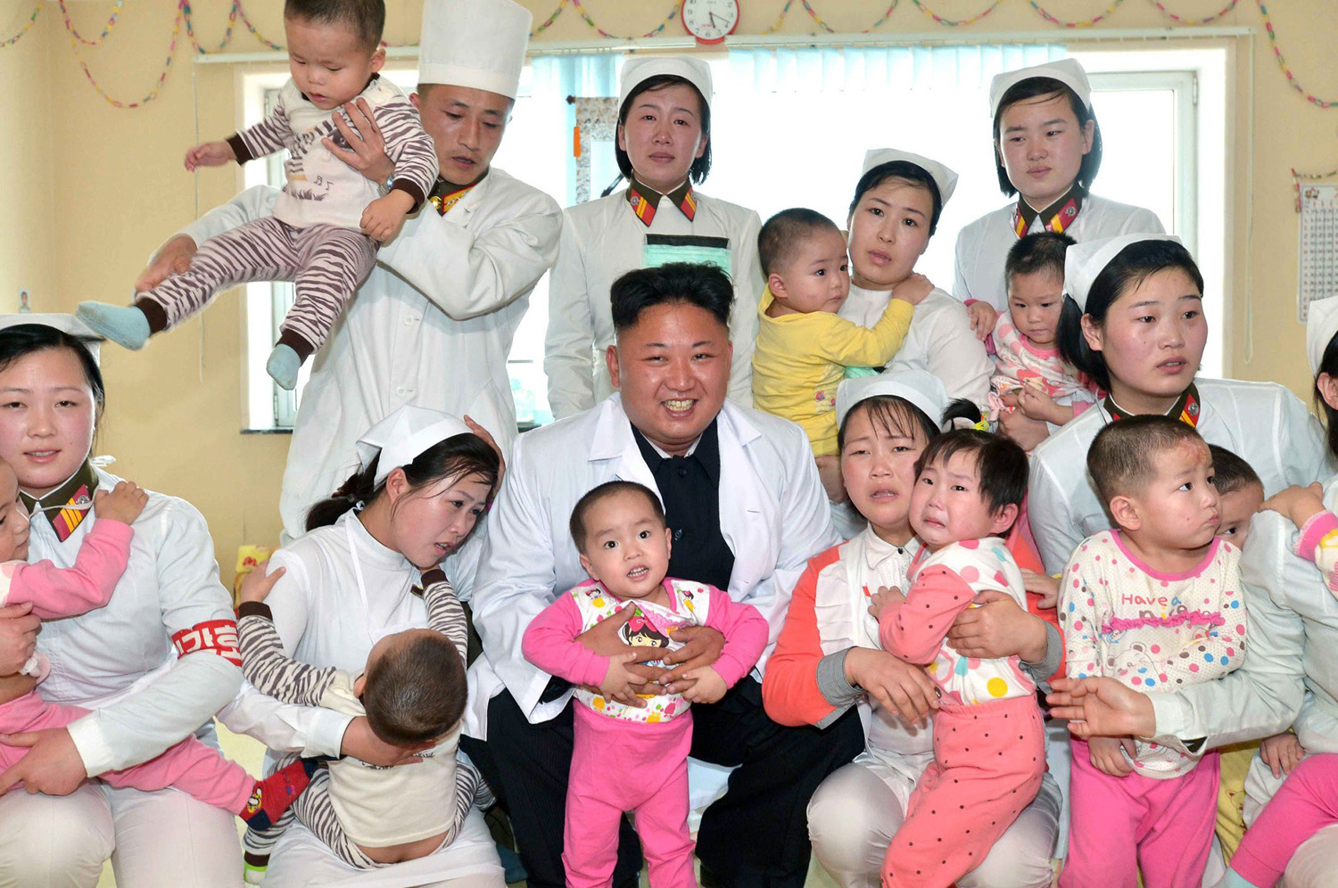 This undated picture released by North Korea's official Korean Central News Agency (KCNA) on May 19, 2014 shows North Korean leader Kim Jong-Un (C) meeting with children at a baby home and orphanage as he visits the Taesongsan General Hospital in Pyongyang.