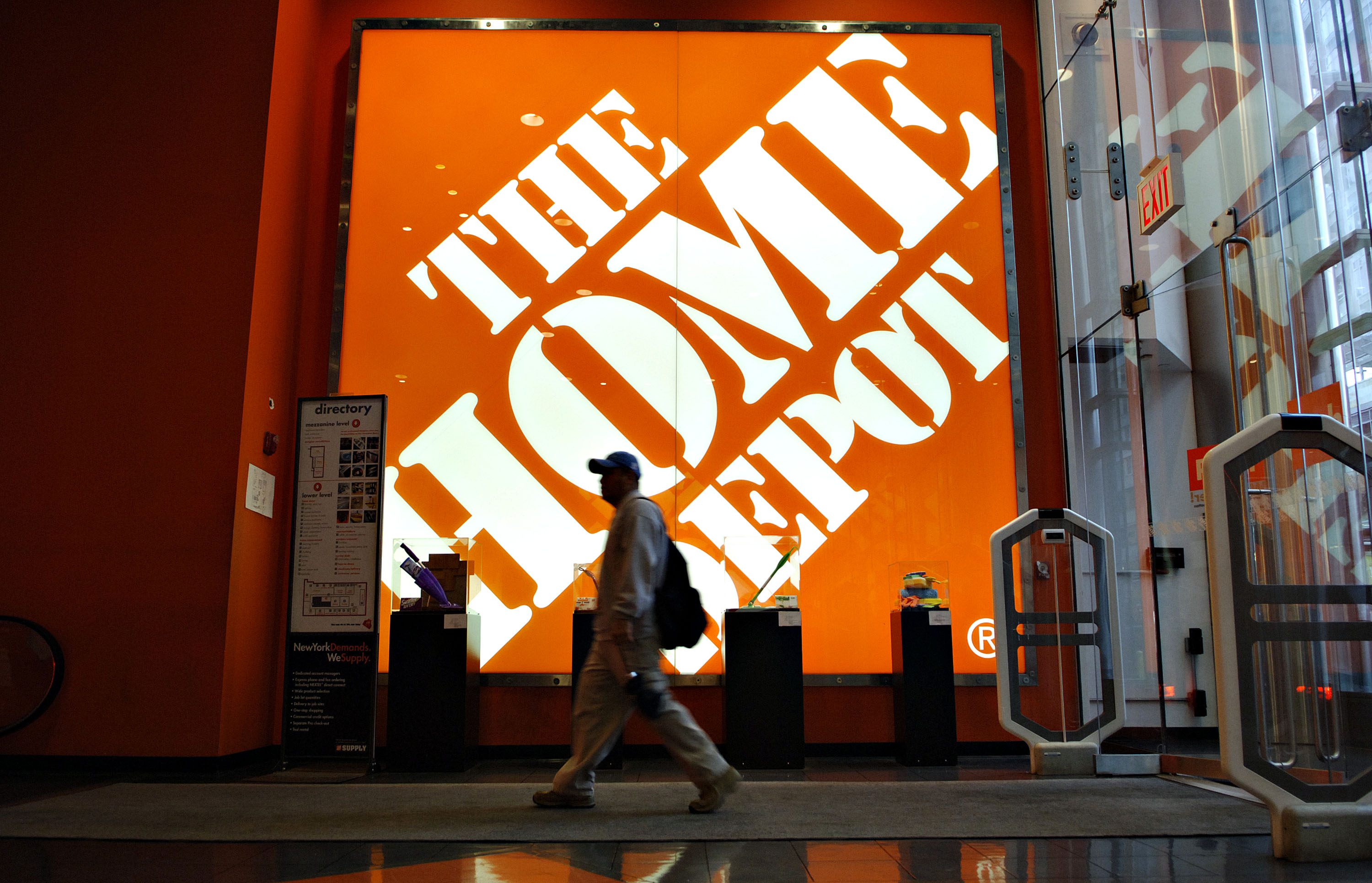 A shopper walks past a large Home Depot logo inside a store in New York on May 16, 2006