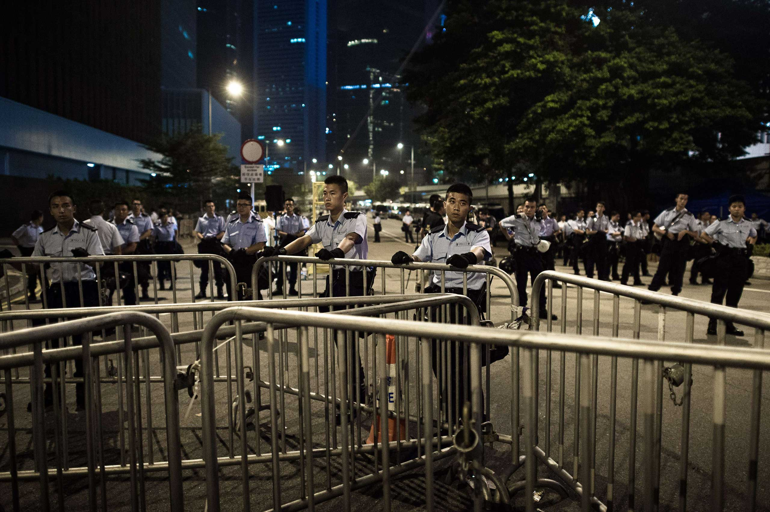 Police stand guard outside the government headquarters in Hong Kong on Oct. 2, 2014, as pro-democracy protesters remain gathered for the fifth day in a push for free elections of the city's leader.