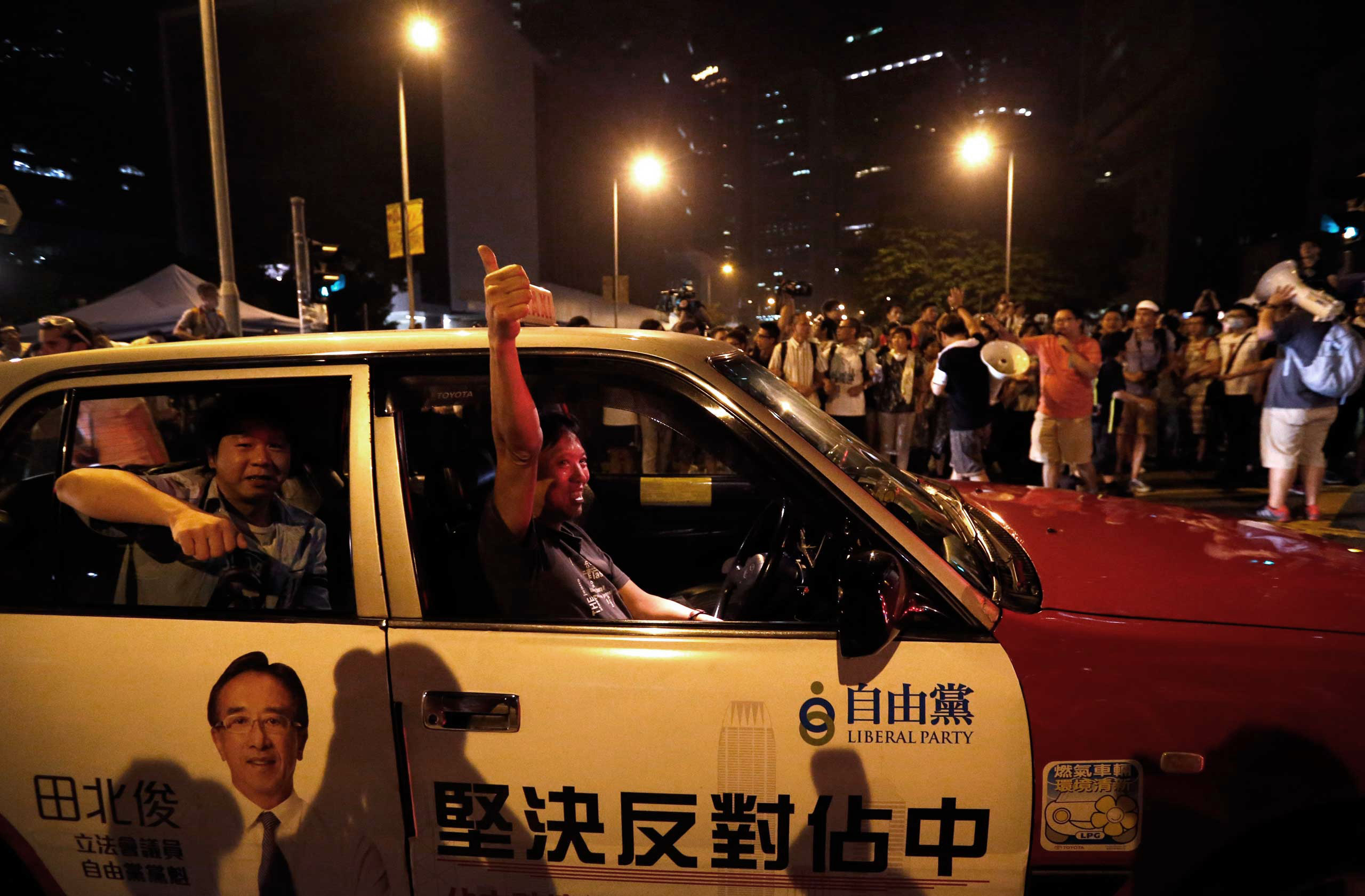 A taxi driver gives a thumbs up to pro-democracy protesters as he drives past the protest site in front of Hong Kong's Chief Executive Leung Chun-ying's office, early on Oct. 3, 2014 in Hong Kong.