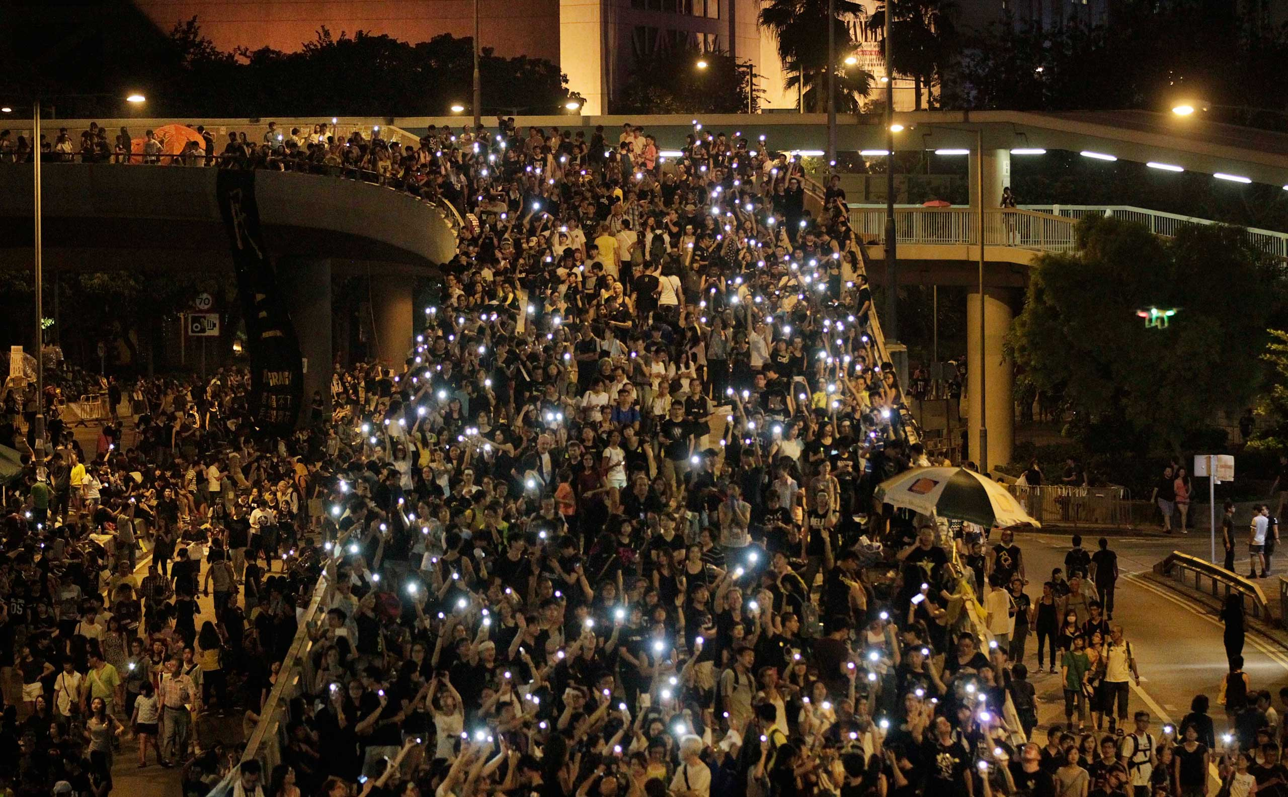 Tens of thousands of pro-democracy demonstrators, some waving lights from mobile phones,  fill the streets in the main finical district of Hong Kong, Oct. 1, 2014.