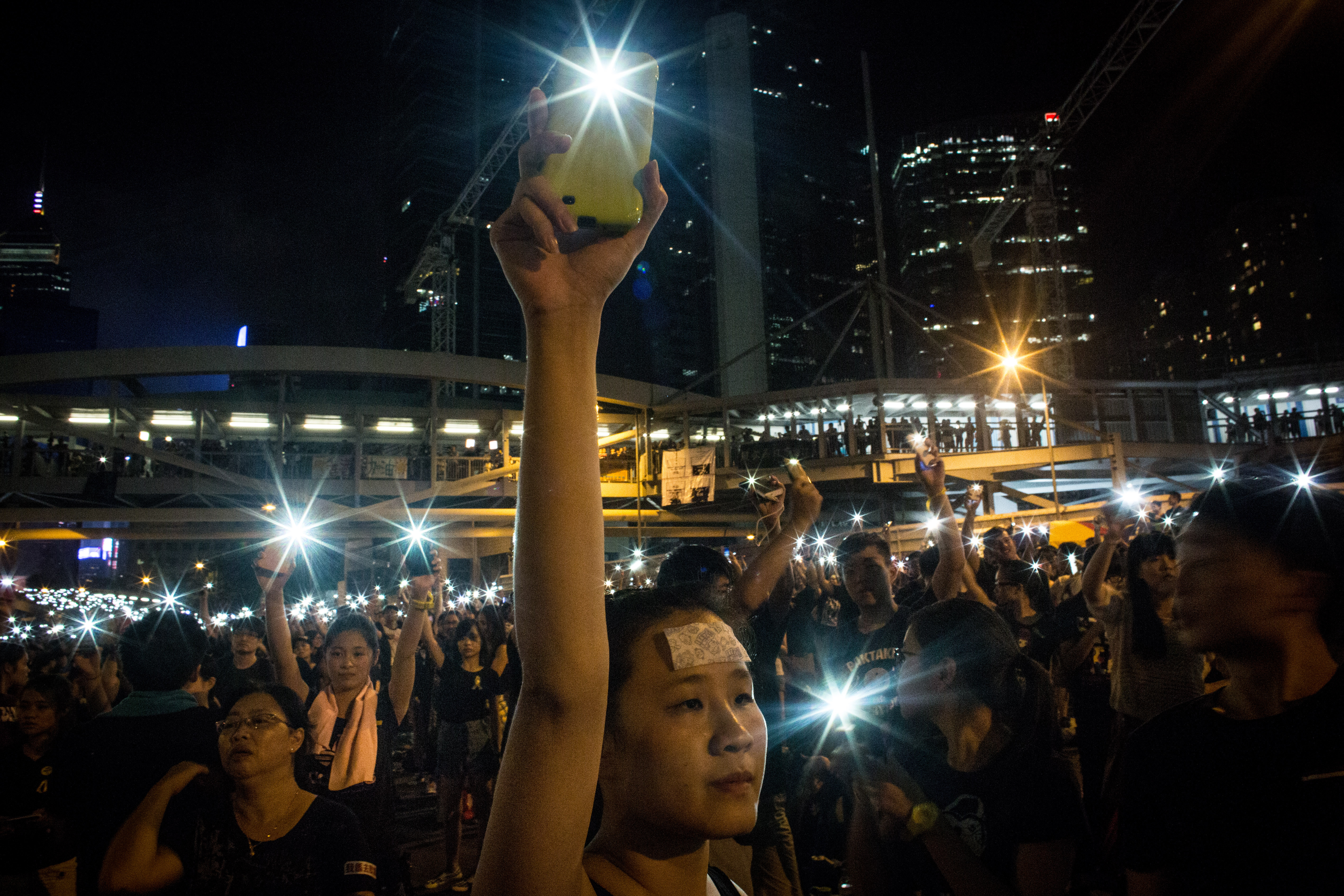 A protester waves her cell phone in the air outside the Hong Kong Government Complexon October 1, 2014 in Hong Kong, Hong Kong.