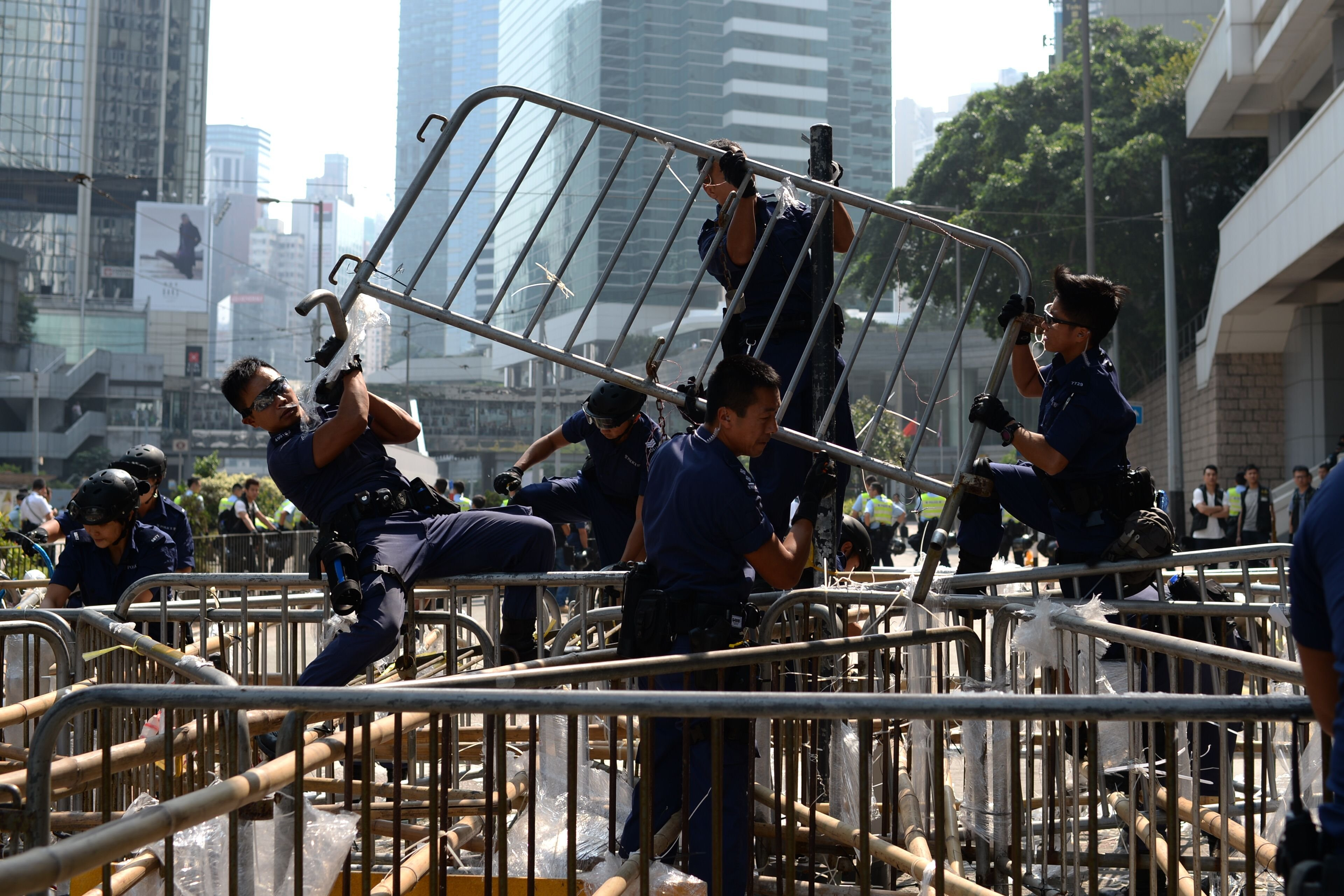 Police officers remove barricades of pro-democracy protestors in the Admiralty district of Hong Kong on Oct. 14, 2014.