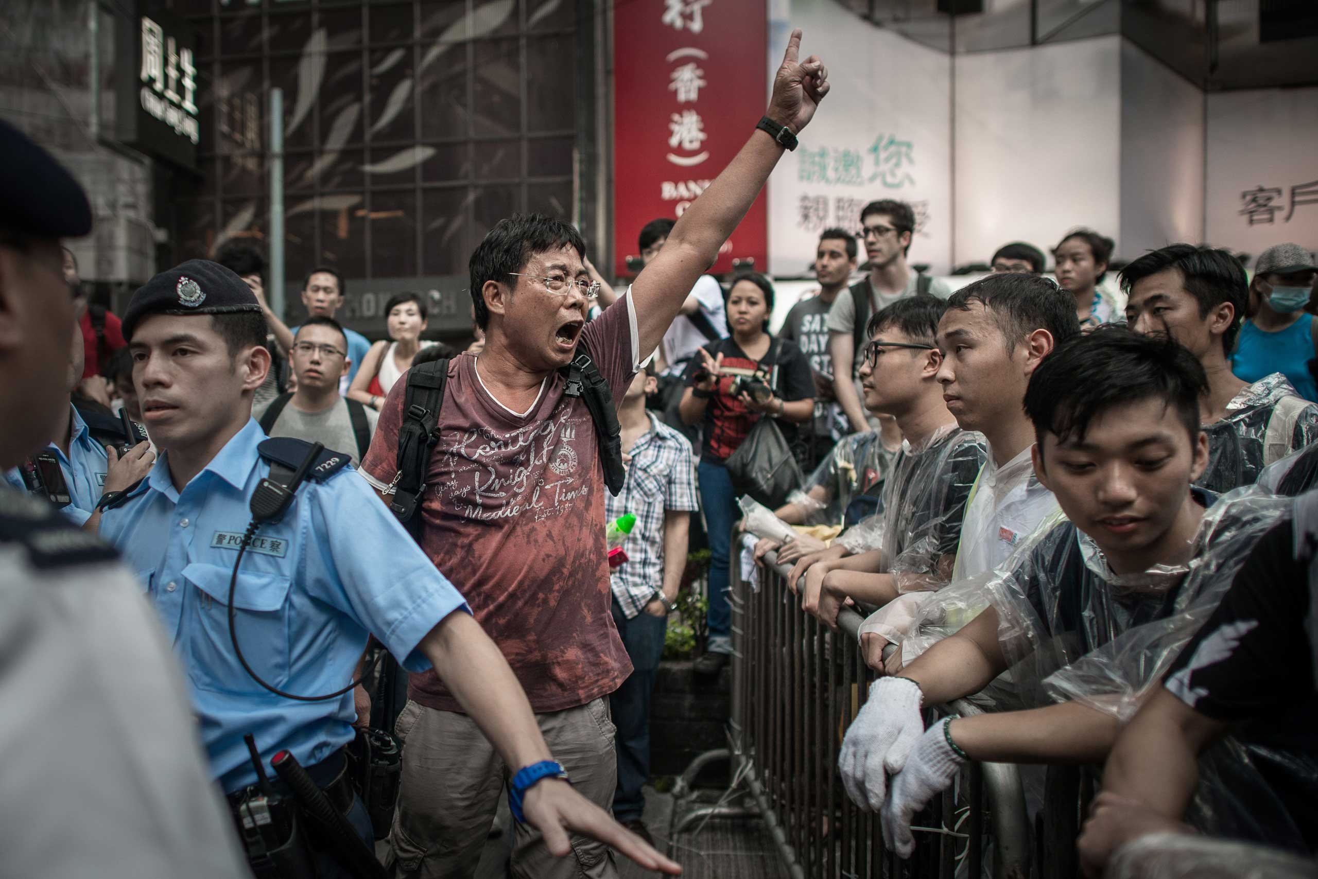 An anti-Occupy protester shouts at pro-democracy demonstrators in an occupied area of Hong Kong on Oct. 3, 2014.