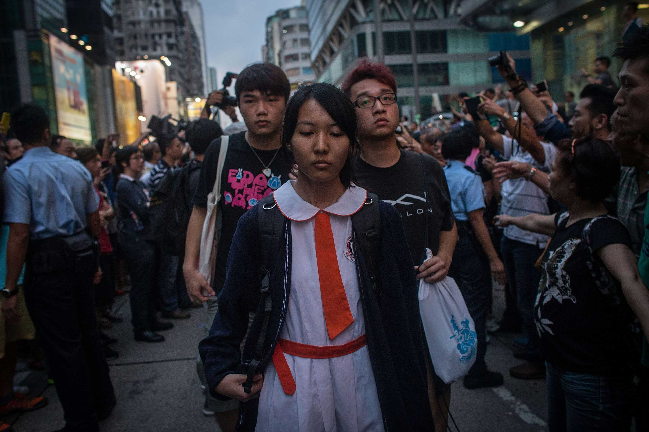 Students and pro-democracy activists leave the protest site as local police hold back local residents and pro-government supporters on Oct. 3, 2014 in Mong Kok, Hong Kong.