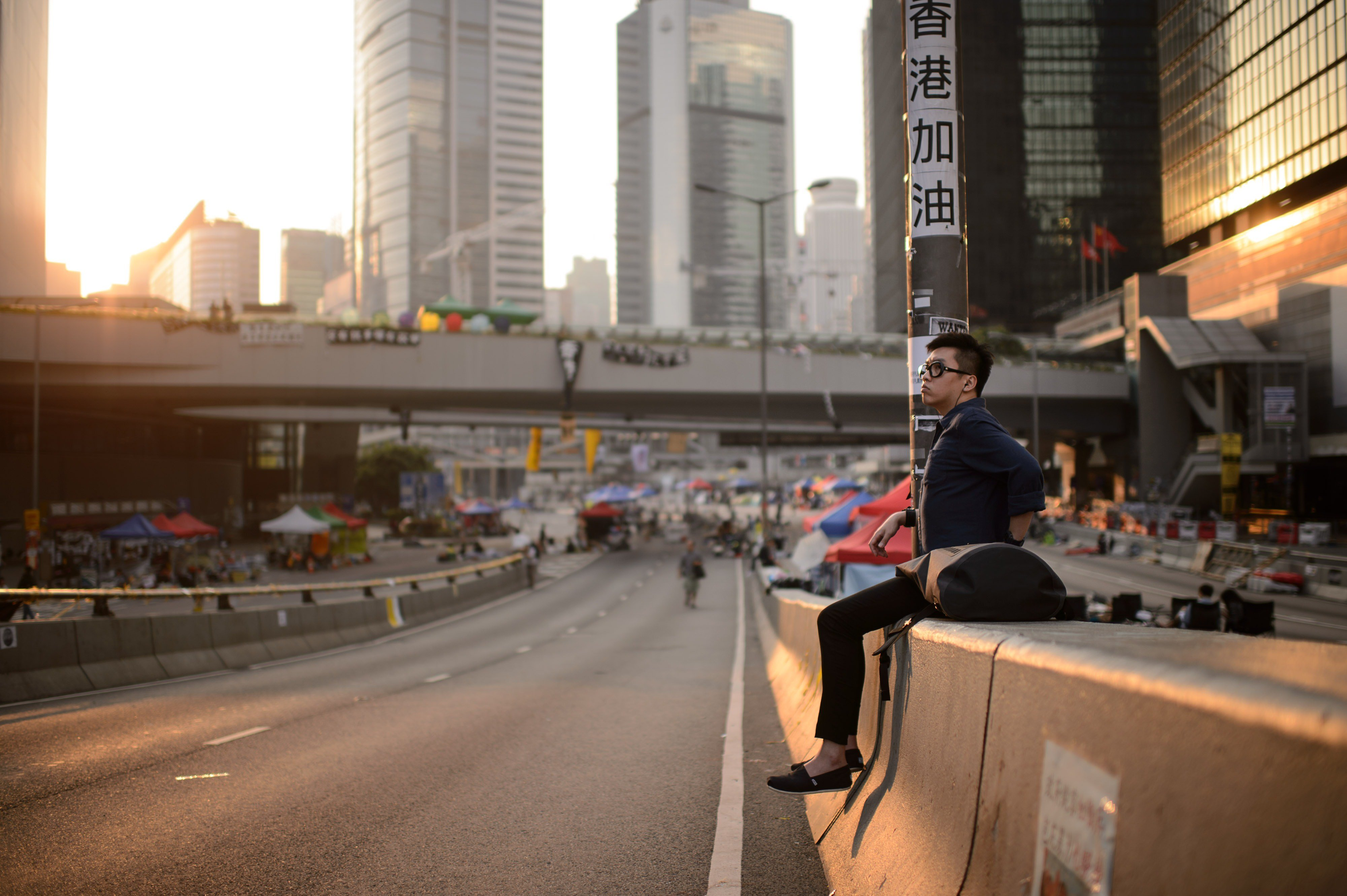 A pro-democracy protester watches the sunrise from an empty road in the Admiralty district of Hong Kong early on Oct. 7, 2014.