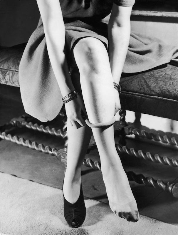 A woman puts on nylon stockings, circa 1940