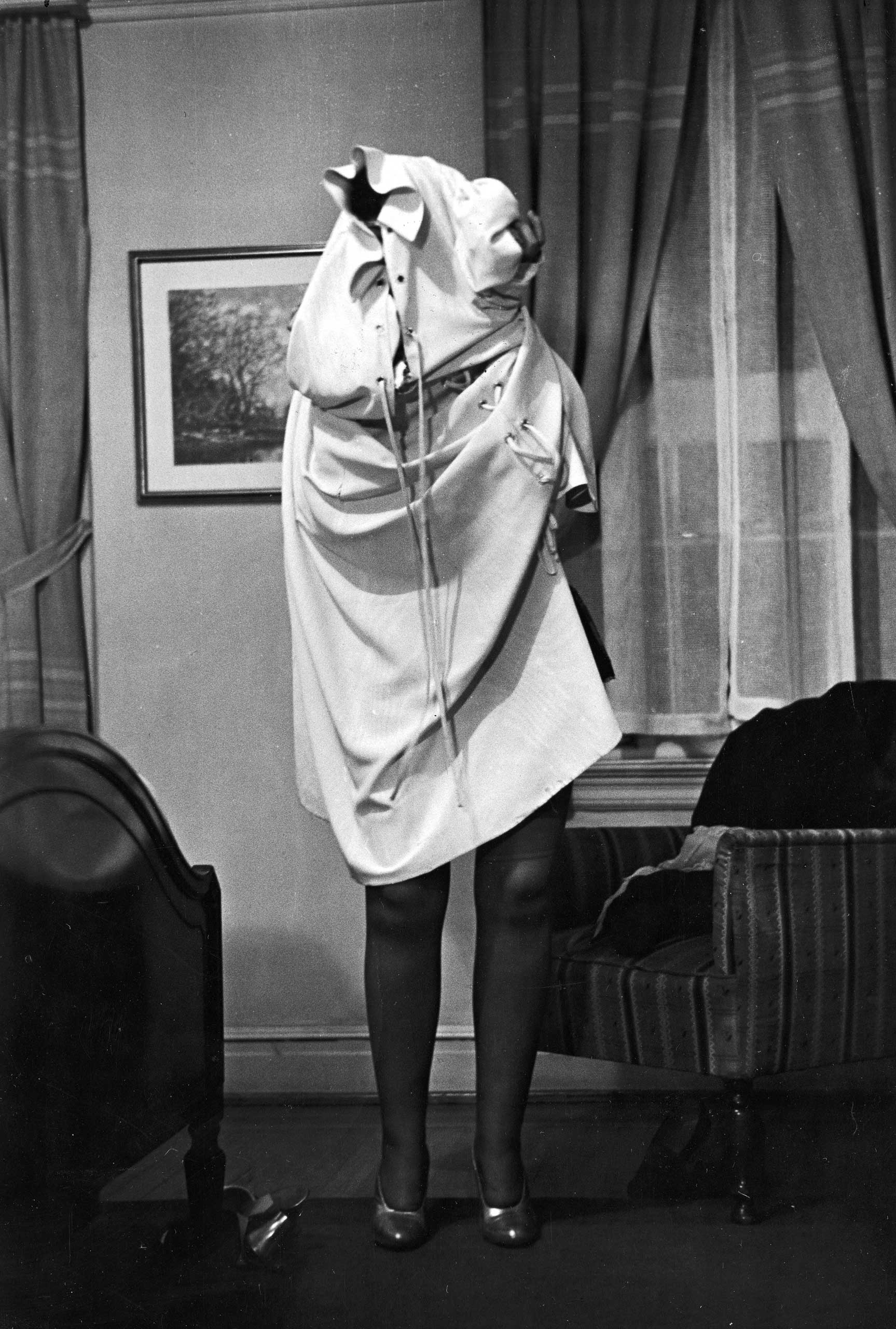 """Professor Connie Fonzlau at the Allen Gilbert School of Undressing in New York demonstrates """"the worst possible method of disrobing,"""" 1937."""