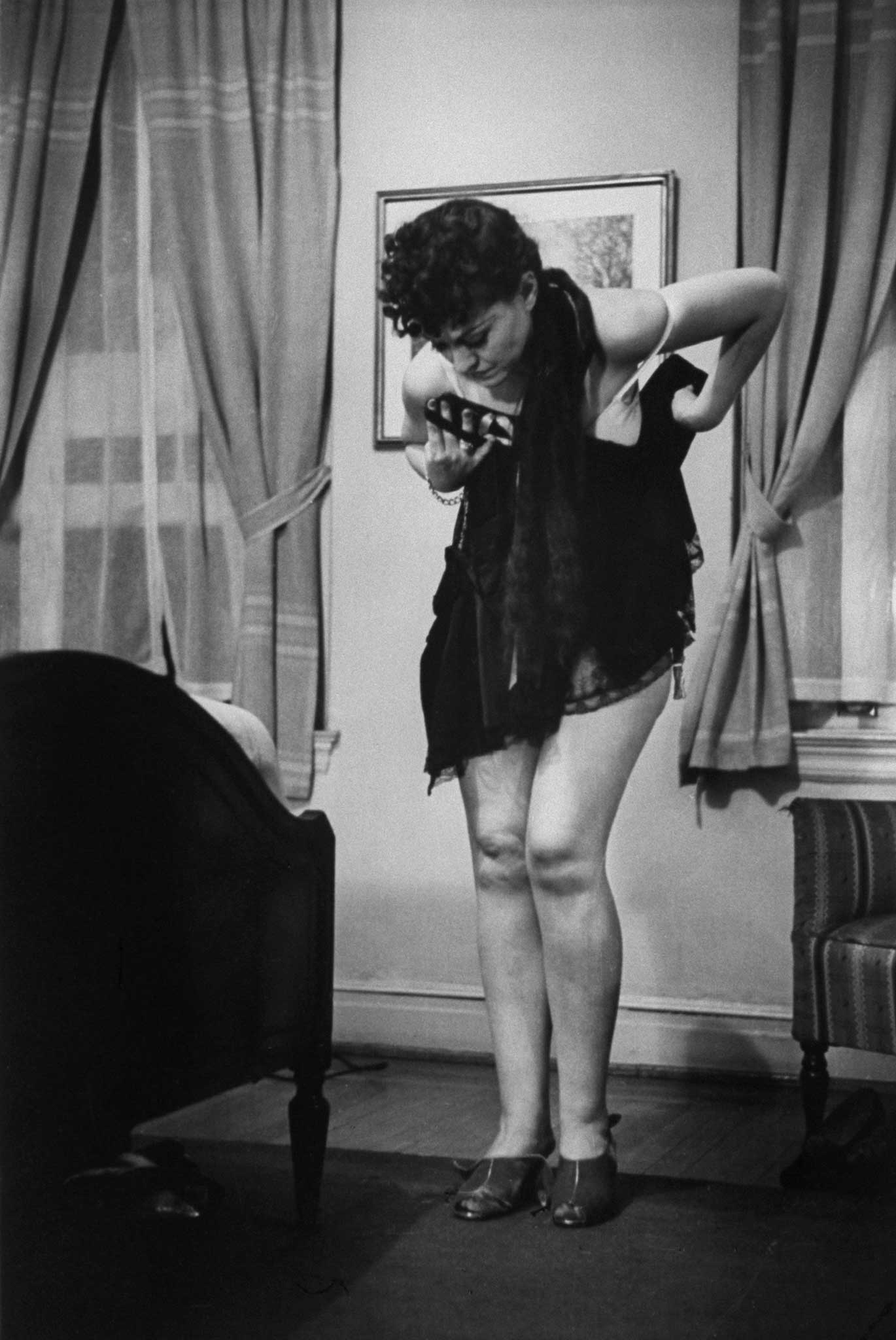"""School of Undressing professor Connie Fonzlau demonstrates the """"unpardonable sin"""" of """"working on two sides at once,"""" 1937."""