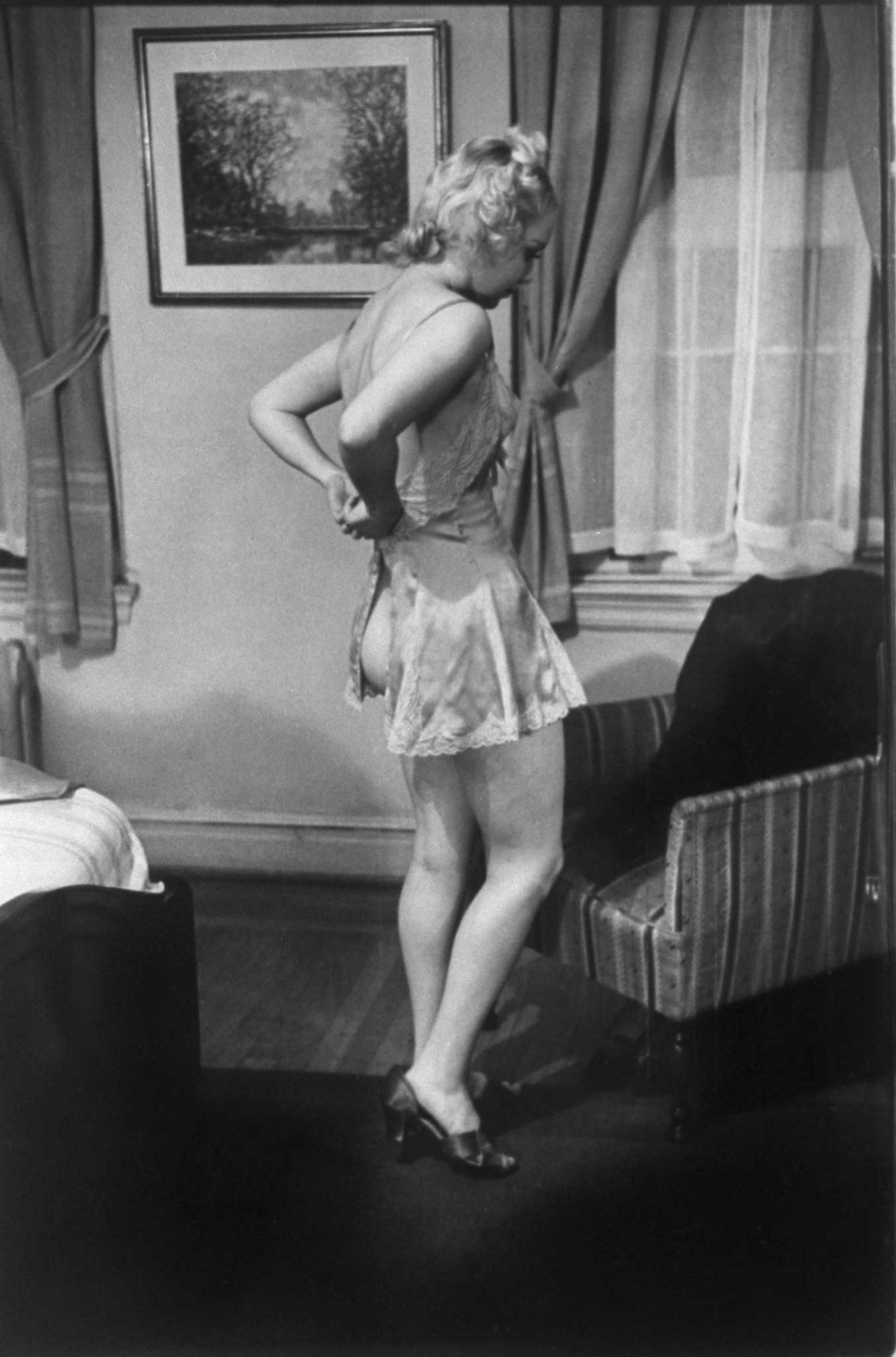 """Burlesque star June St. Clair demonstrates """"how wives should undress in front of their husbands"""" during a class at the Allen Gilbert School of Undressing in New York, 1937."""
