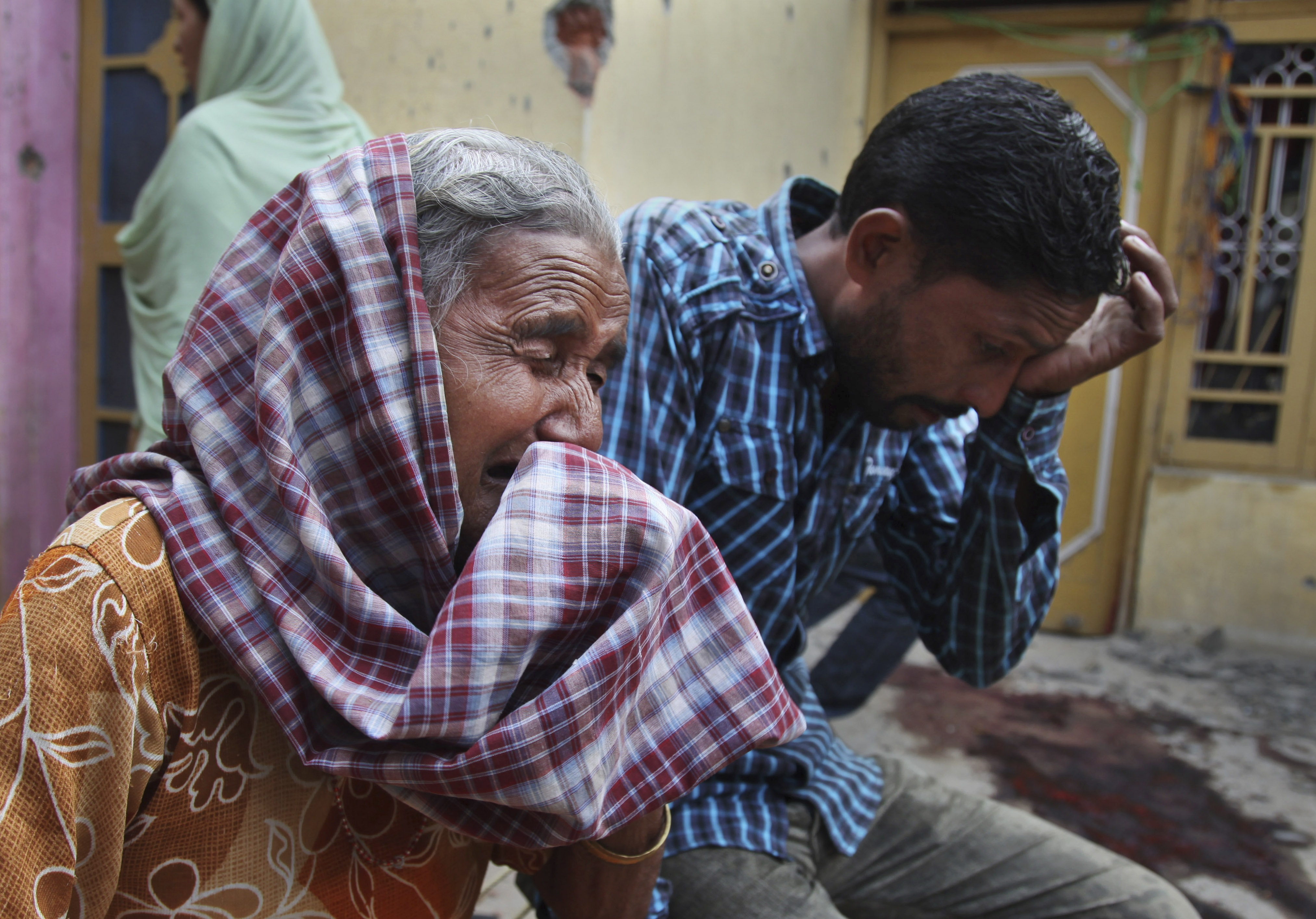 Relatives of Rajesh Kumar, who was killed in mortar shell firing allegedly from Pakistan's side, weep inside their house at Masha Da Kothe village, near the India-Pakistan border, about 30 miles from Jammu, India, on Oct. 6, 2014
