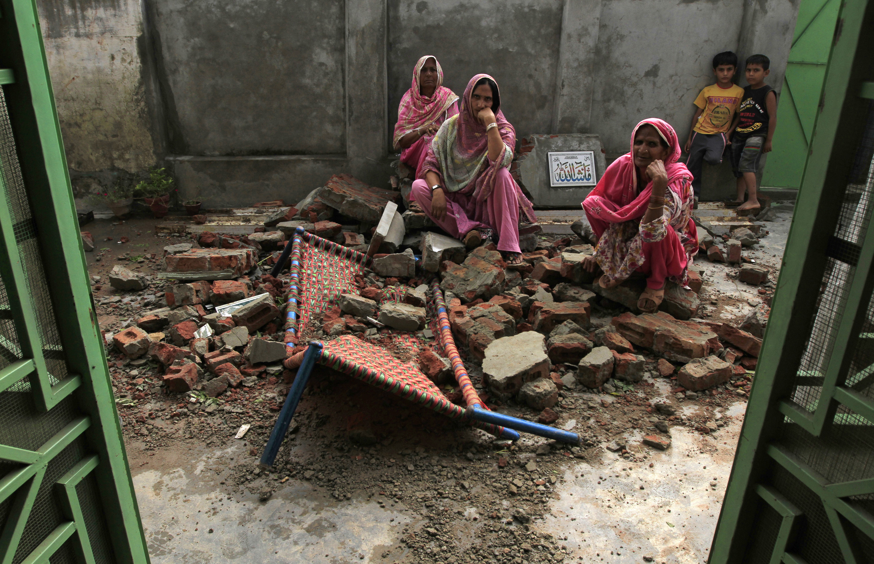 Villagers sit on the debris of their house after it was damaged during the recent exchange of fire between Pakistan and India at the Pakistani border town of Dhamala Hakimwala on Oct. 8, 2014