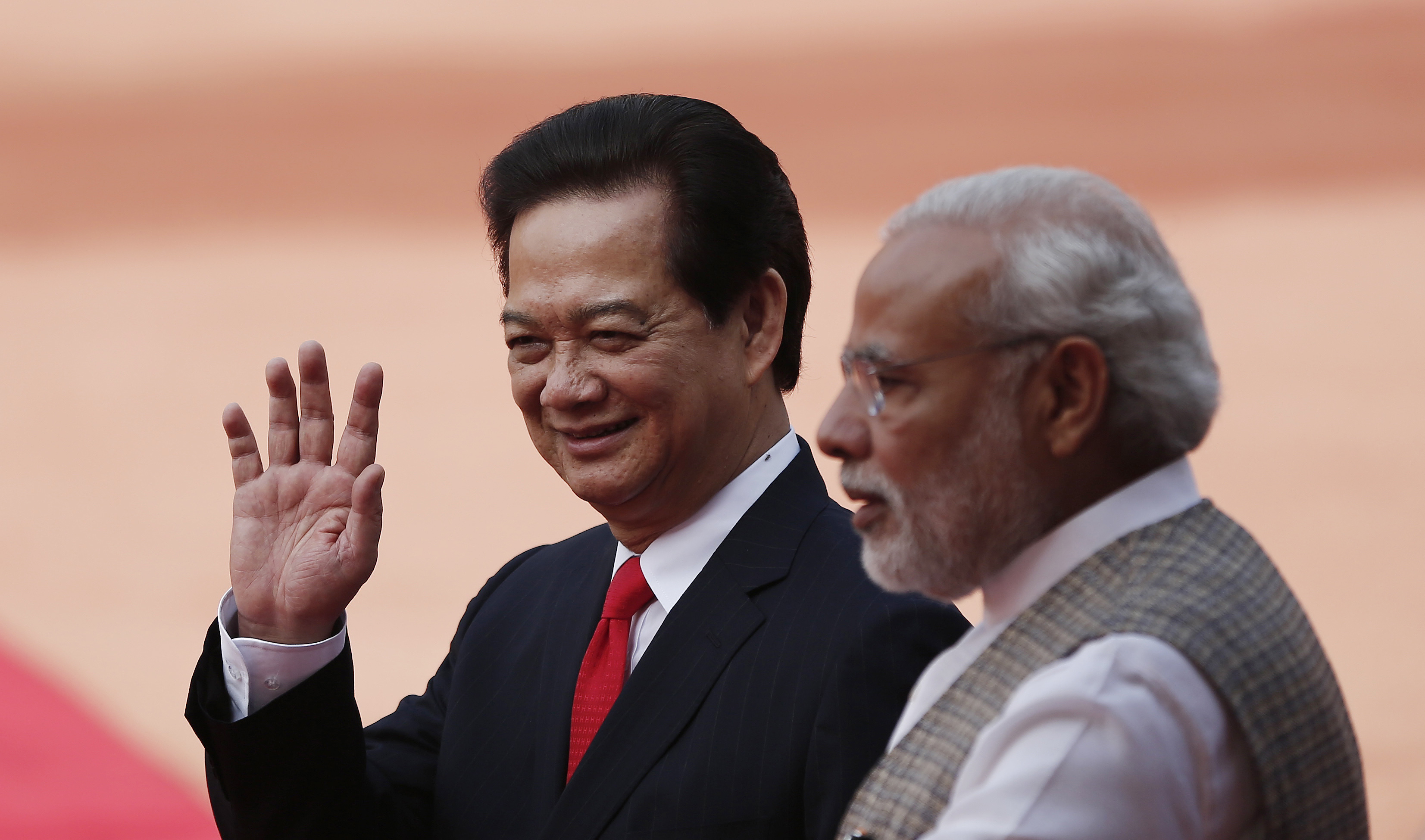 Vietnam's Prime Minister Nguyen Tan Dung waves next to his Indian counterpart Narendra Modi during Dung's ceremonial reception at the forecourt of India's presidential palace in New Delhi on Oct. 28, 2014