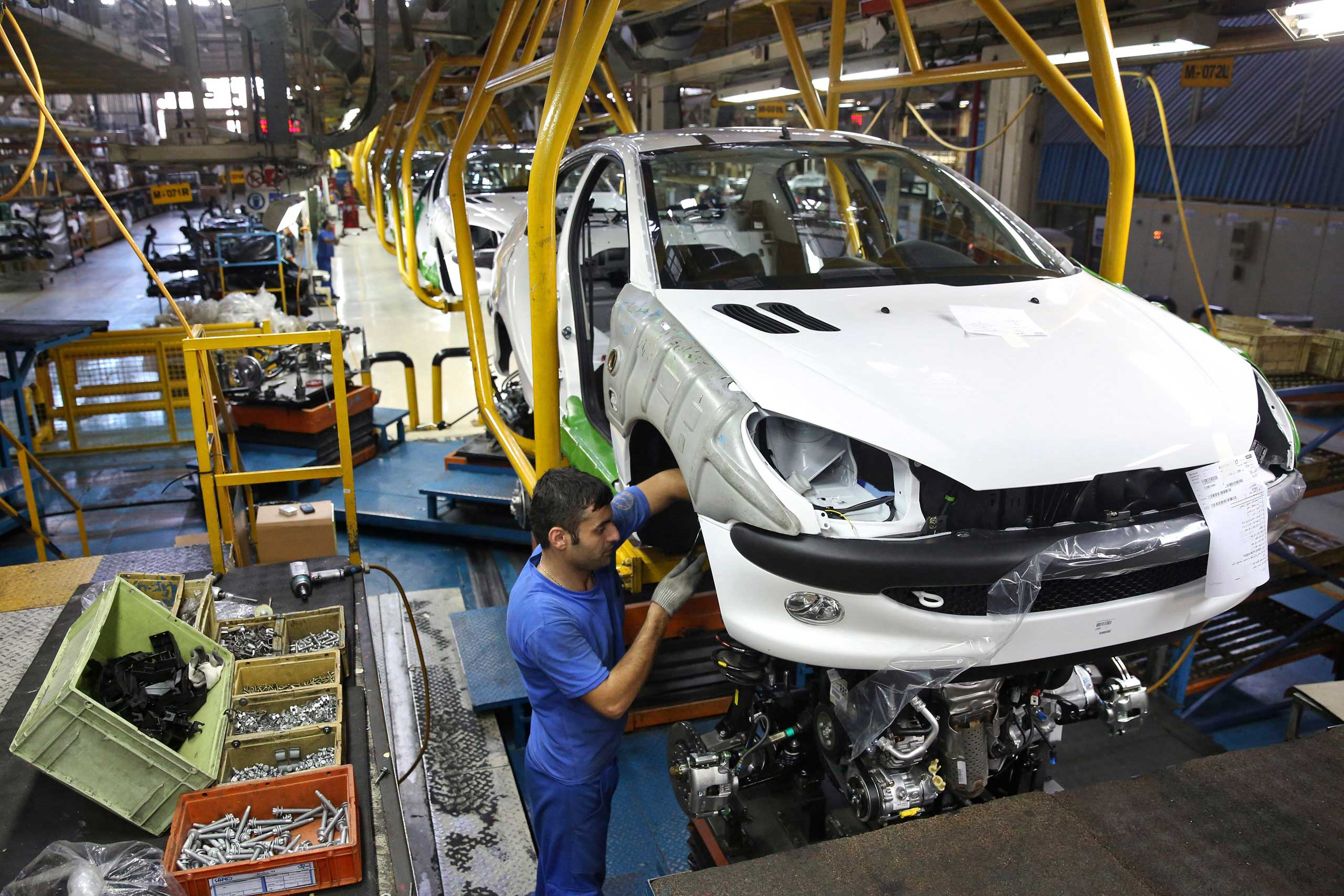 An Iranian worker assembles a Peugeot 206 at the state-run Iran-Khodro automobile manufacturing plant near Tehran, Iran, Oct. 11, 2014.