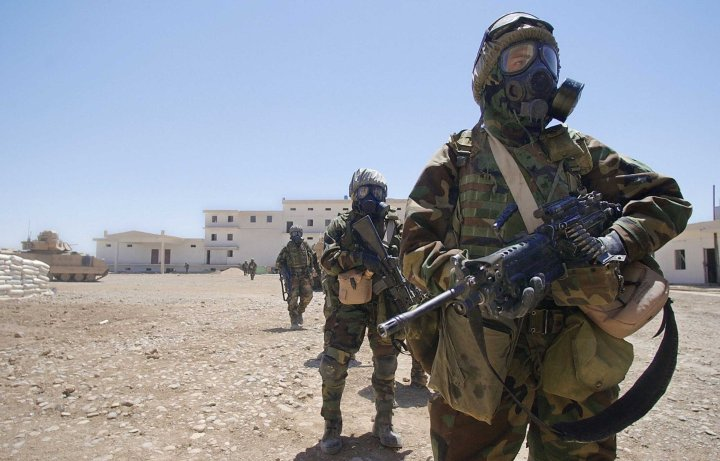 US Army soldiers wearing their full chemical protection suits walk inside the courtyard of an industrial complex they secured which they thought was a possible site for weapons of mass destruction in the central Iraqi town of Baquba in May 2003.