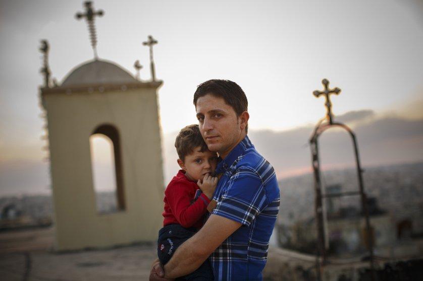 Radwan Shamra, Iraqi Christian refugee, with his son, Martin, 3, on the roof of St. Ephraim Syrian Orthodox Church in Amman, Jordan, Oct. 1, 2014.