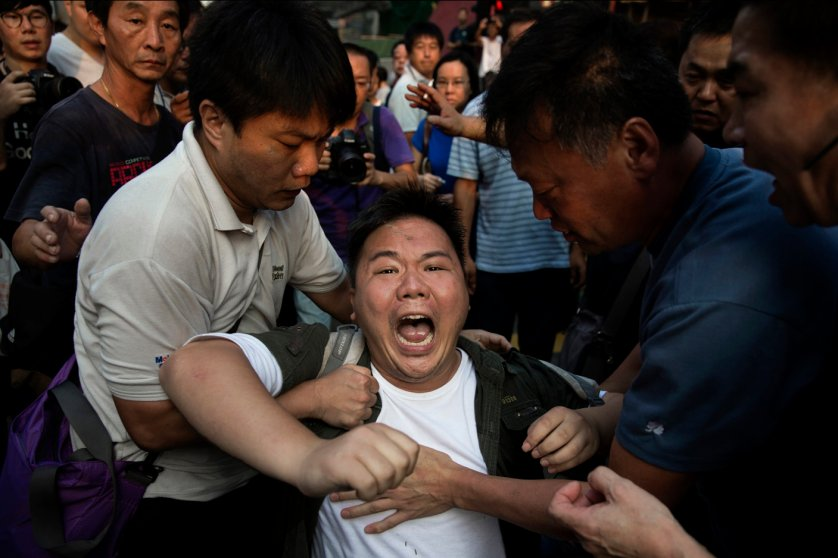 A pro-democracy protestor yells as he is attacked by an anti occupy crowd during democracy demonstrations in the Mong Kong district of Hong Kong.