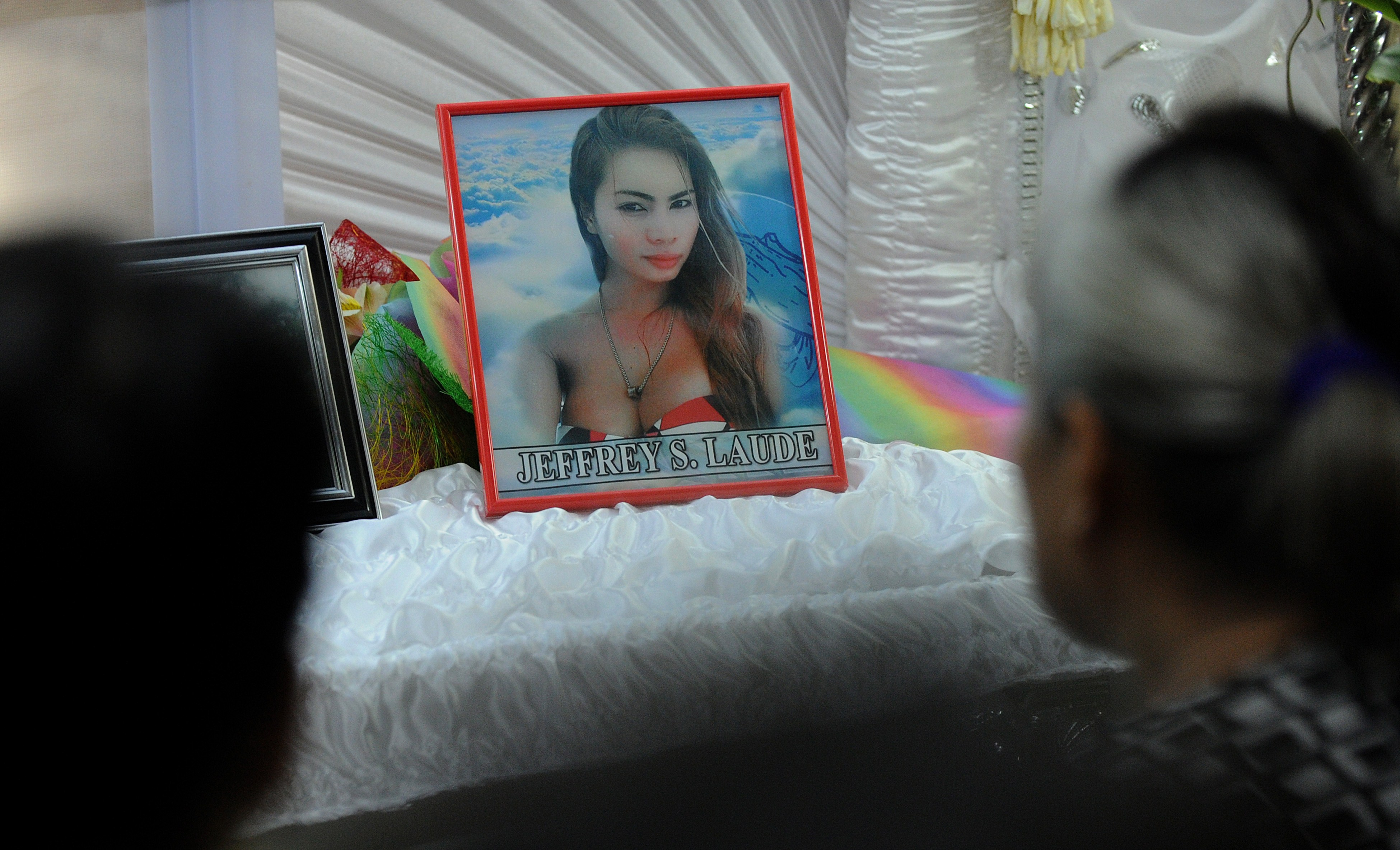 Friends and relatives of Jeffrey Laude, a Filipino transgender woman who went by Jennifer, look at her coffin in the northern Philippine city of Olongapo on Oct. 14, 2014.
