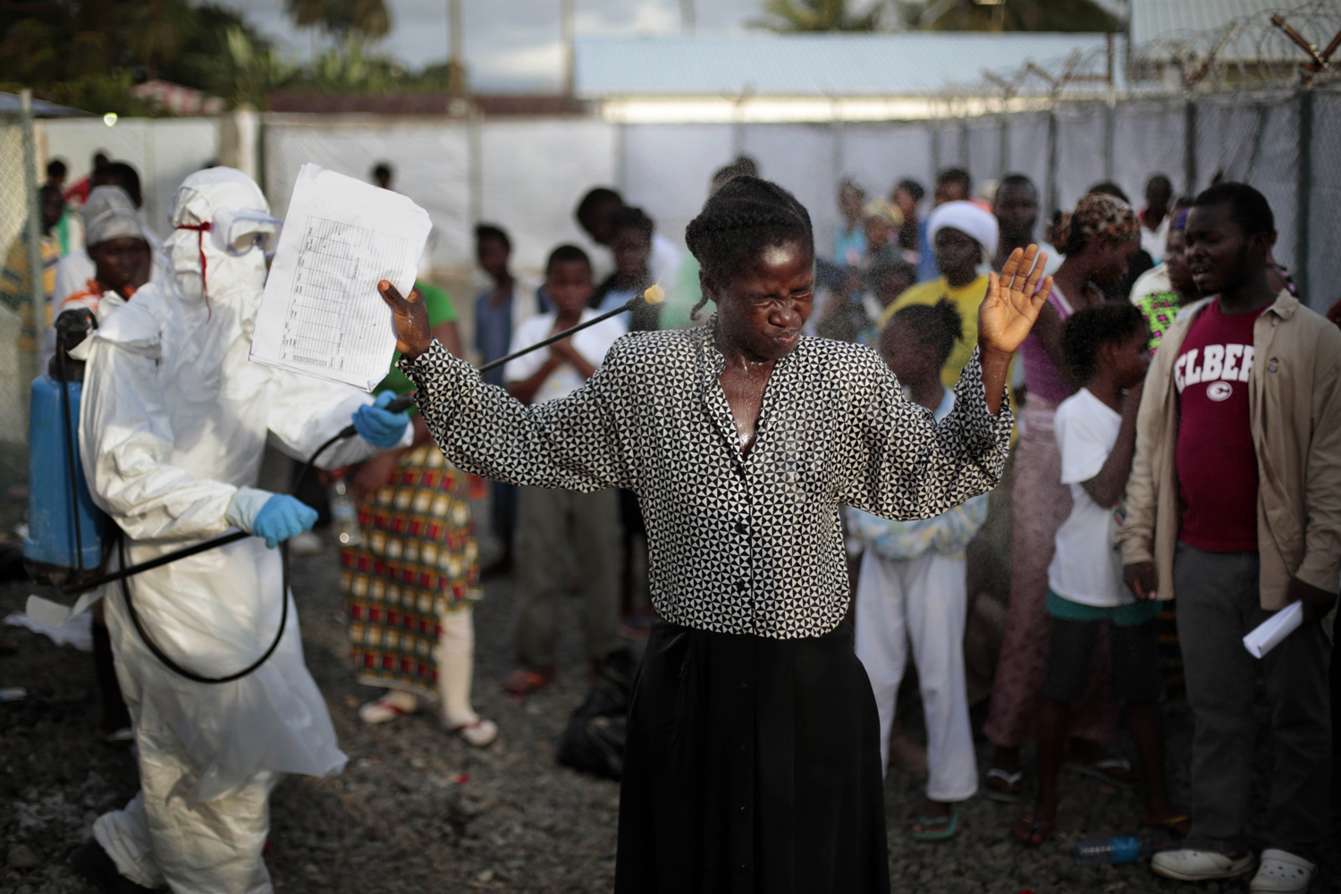 A woman being discharged from the Island Clinic Ebola treatment center in Monrovia, Liberia, is sprayed with disinfectant, Sept. 30, 2014.