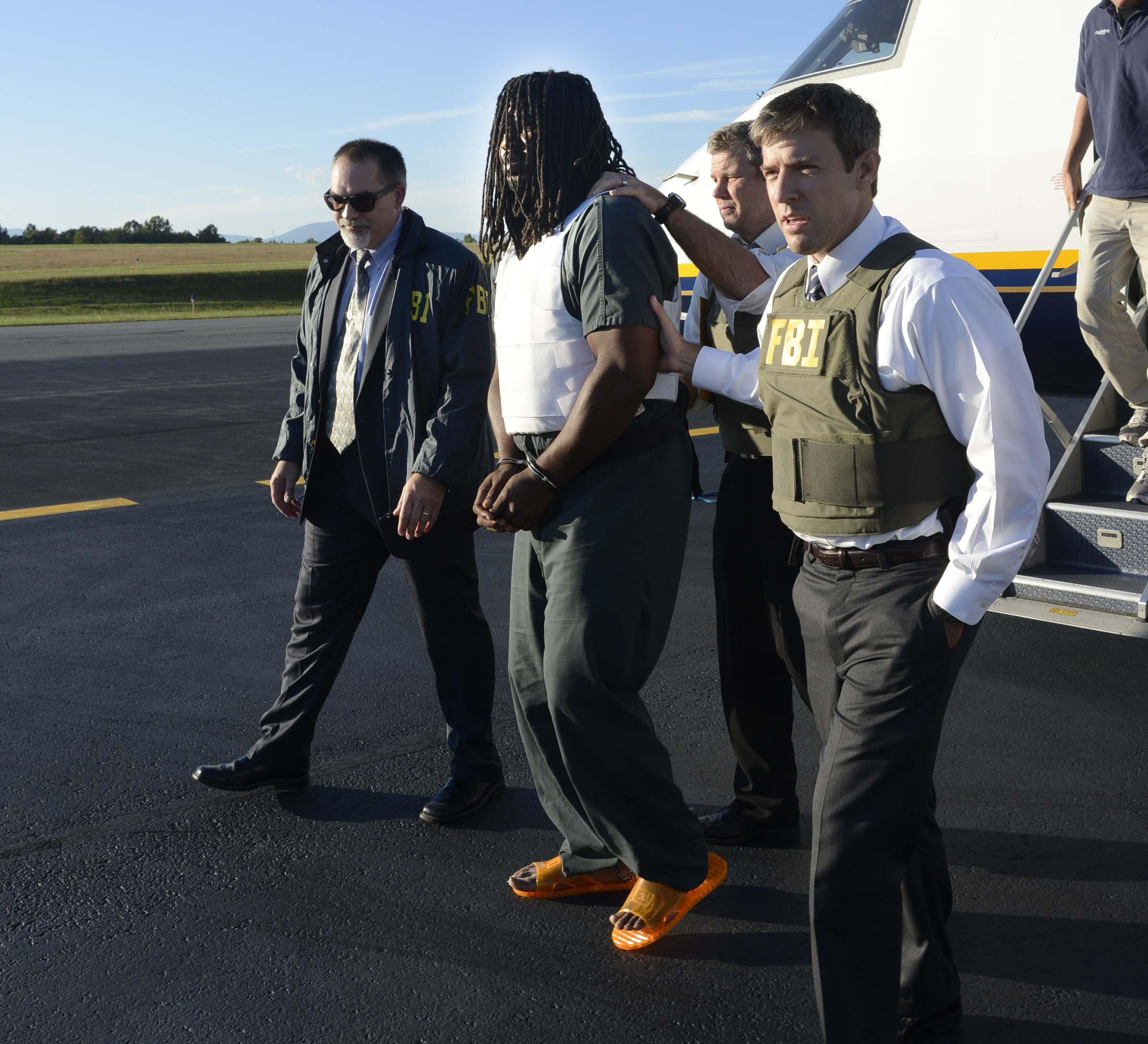 From left: FBI agents escort Jesse Matthew into the custody of the Charlottesville Police Department September 26, 2014 in Charlottesville, Virginia.