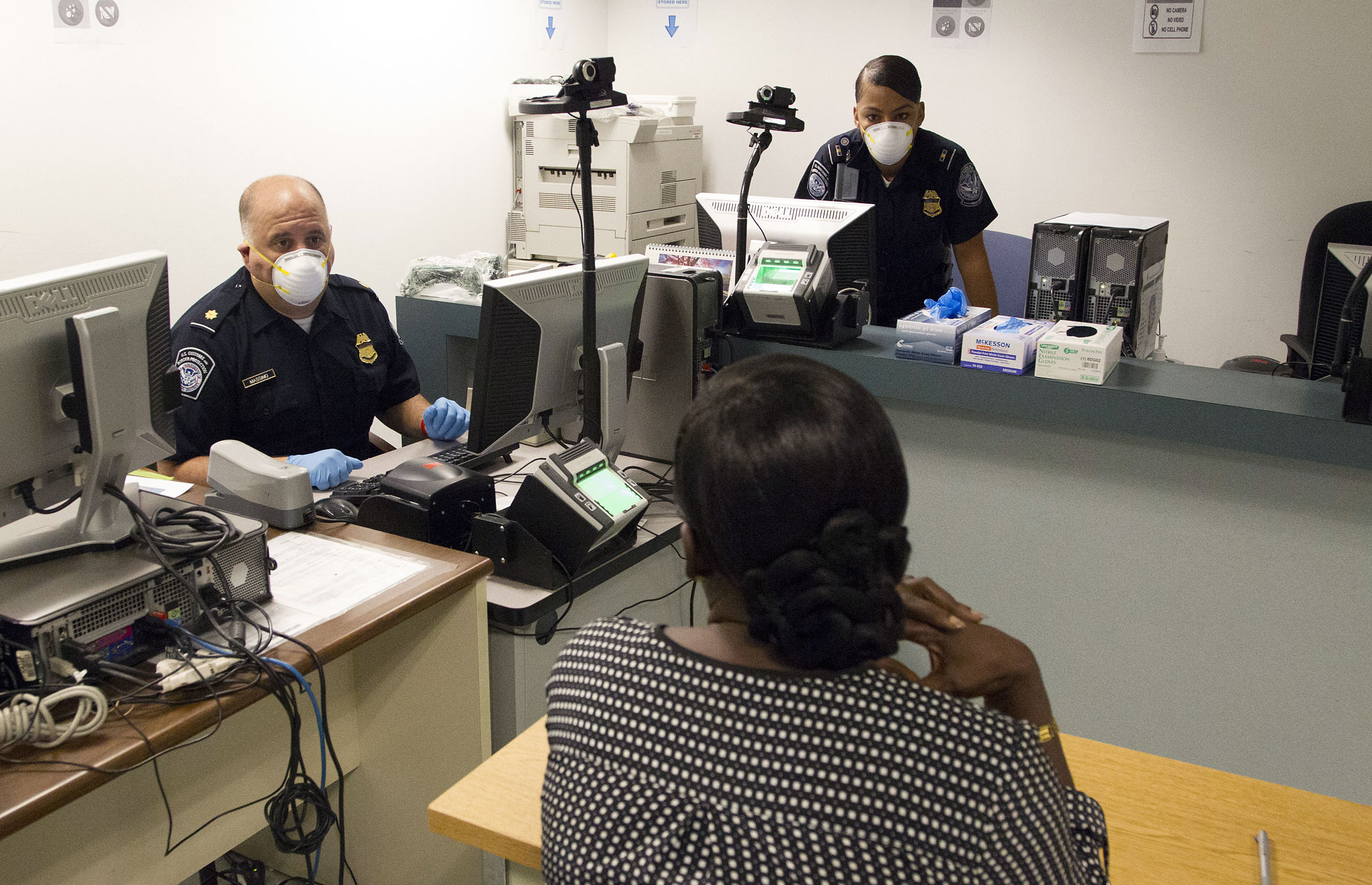 U.S. Customs and Border Protection Officers conduct enhanced screening at JFK International Airport in New York City on October 11, 2014.
