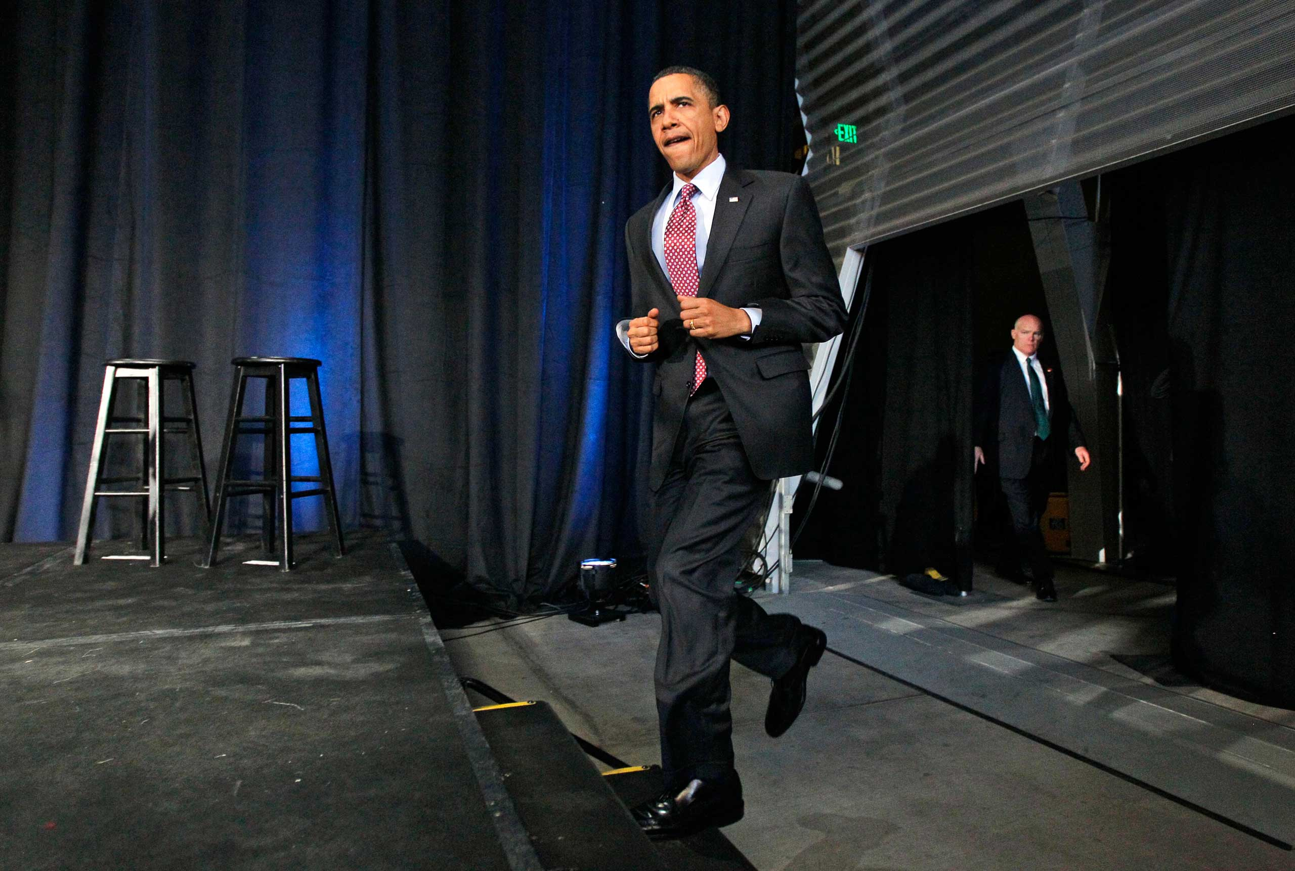 President Barack Obama jogs up the steps to speak at a fundraiser for the Democratic National Committee and Sen. Barbara Boxer, with Clancy watching closely from the wings, at the California Science Center in Los Angeles, April 19, 2010.