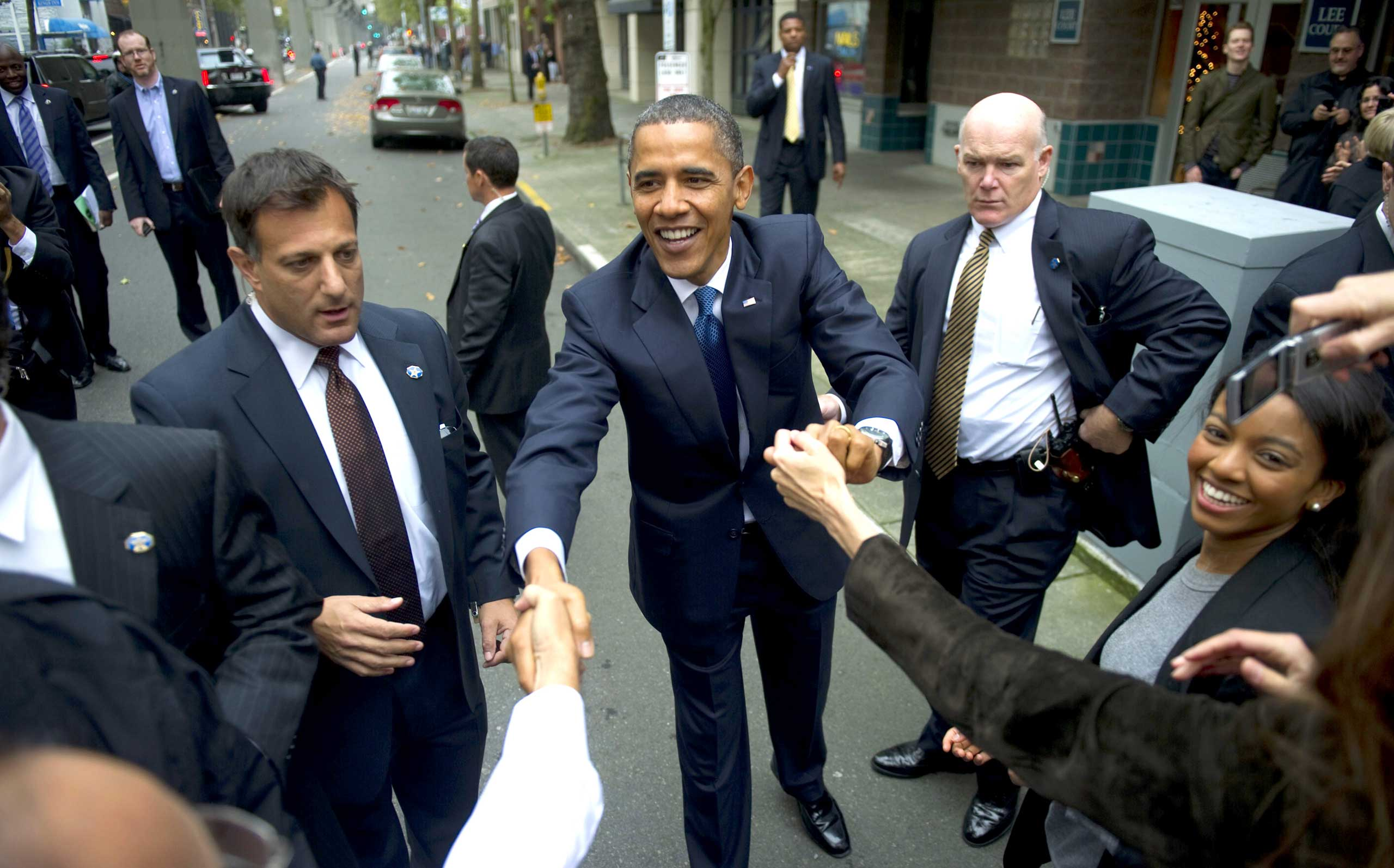 Eyeing those extended arms warily, Clancy keeps hold on President Barack Obama as he shakes hands with people outside of the Top Pot Doughnuts shop in Seattle on Oct. 21, 2010.
