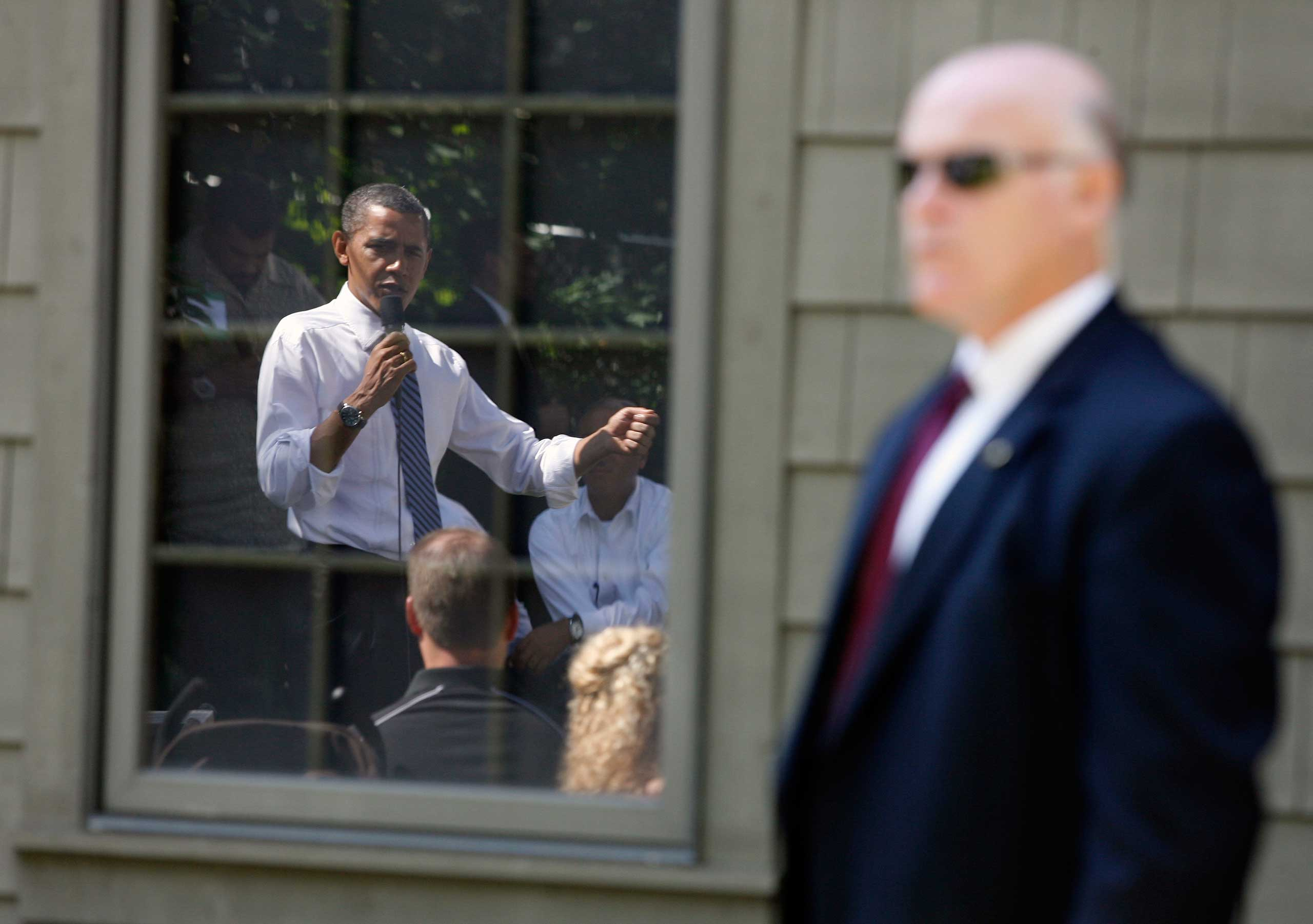 Clancy in the foreground, as Obama is reflected in a garage window in a backyard at the Weithman family home on Aug 18, 2010 in Columbus, Ohio.